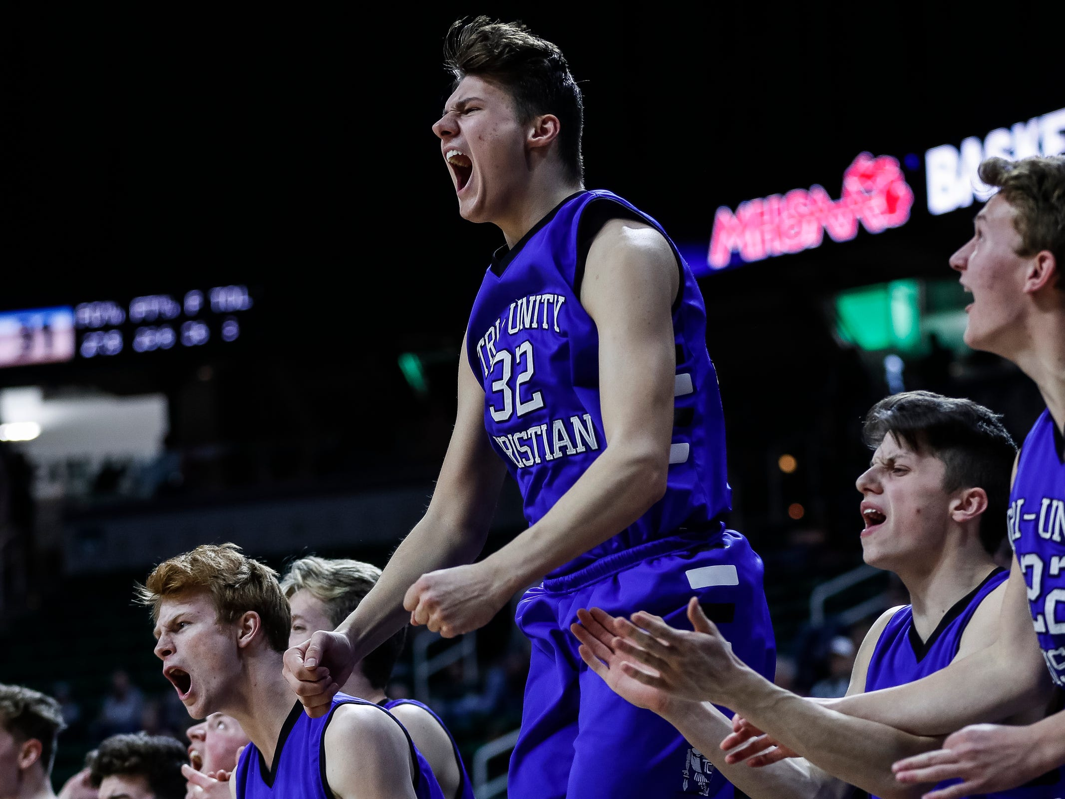 Wyoming Tri-unity Christian's Austin Treece (32) jumps up as he cheers for his teammates against Frankfort during the second half of MHSAA Division 4 semifinal at the Breslin Center in East Lansing, Thursday, March 14, 2019.