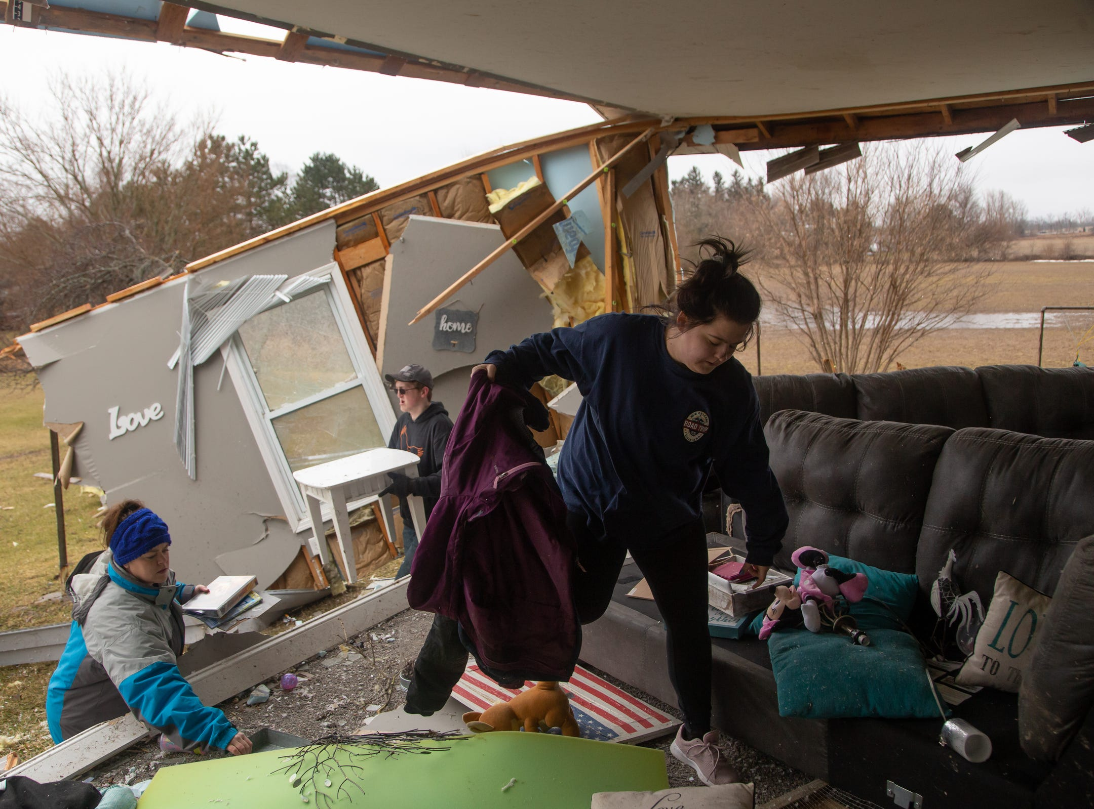 """Mackenzie Weaver helps clear items from the living room area of her mother's home in Bancroft on Friday, March 15, 2019that was damaged after a tornado moved through Shiawassee County overnight. """"When I came to the house today I wasn't expecting it to be as bad as it really is. It freaked me out it really did. I was crying hysterically. I called in to work today so I could help them out,"""" Weaver said.Weavers mother and her six foster children were in the house at the time of the tornado hitting and got a call from her mother-in-law to get in the basement seconds before it hit."""
