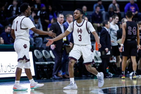 U-D Jesuit's Jordan Montgomery (3) high fives teammate Julian Dozier (1) at a timeout during the first half of MHSAA Division 1 semifinal against Okemos at the Breslin Center in East Lansing, Friday, March 15, 2019.