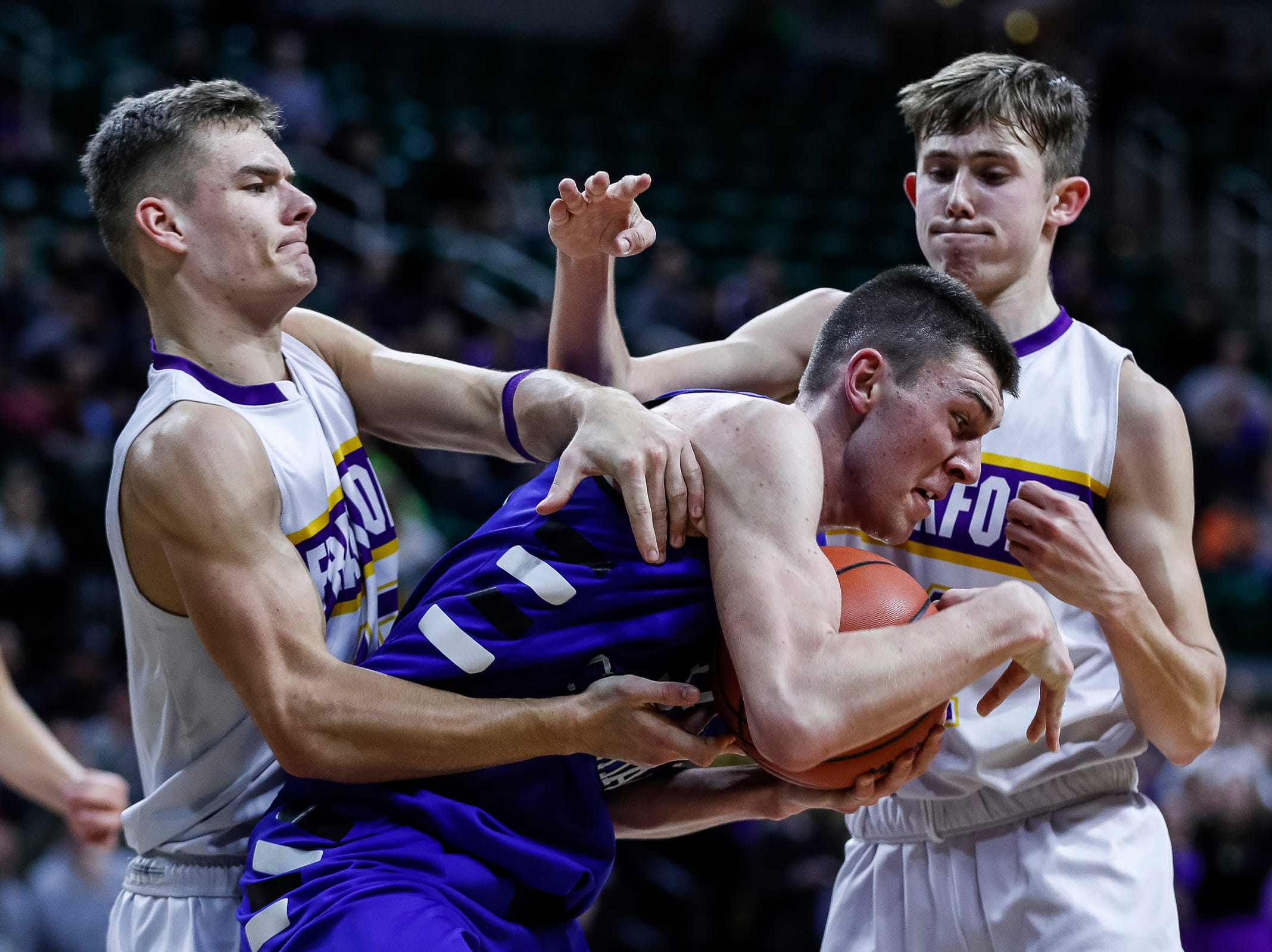 Wyoming Tri-unity Christian's Elijah Badgero (34) tries to protect the ball from Frankfort's Conner Smith (15) and Will Newbold (14) during the second half of MHSAA Division 4 semifinal at the Breslin Center in East Lansing, Thursday, March 14, 2019.