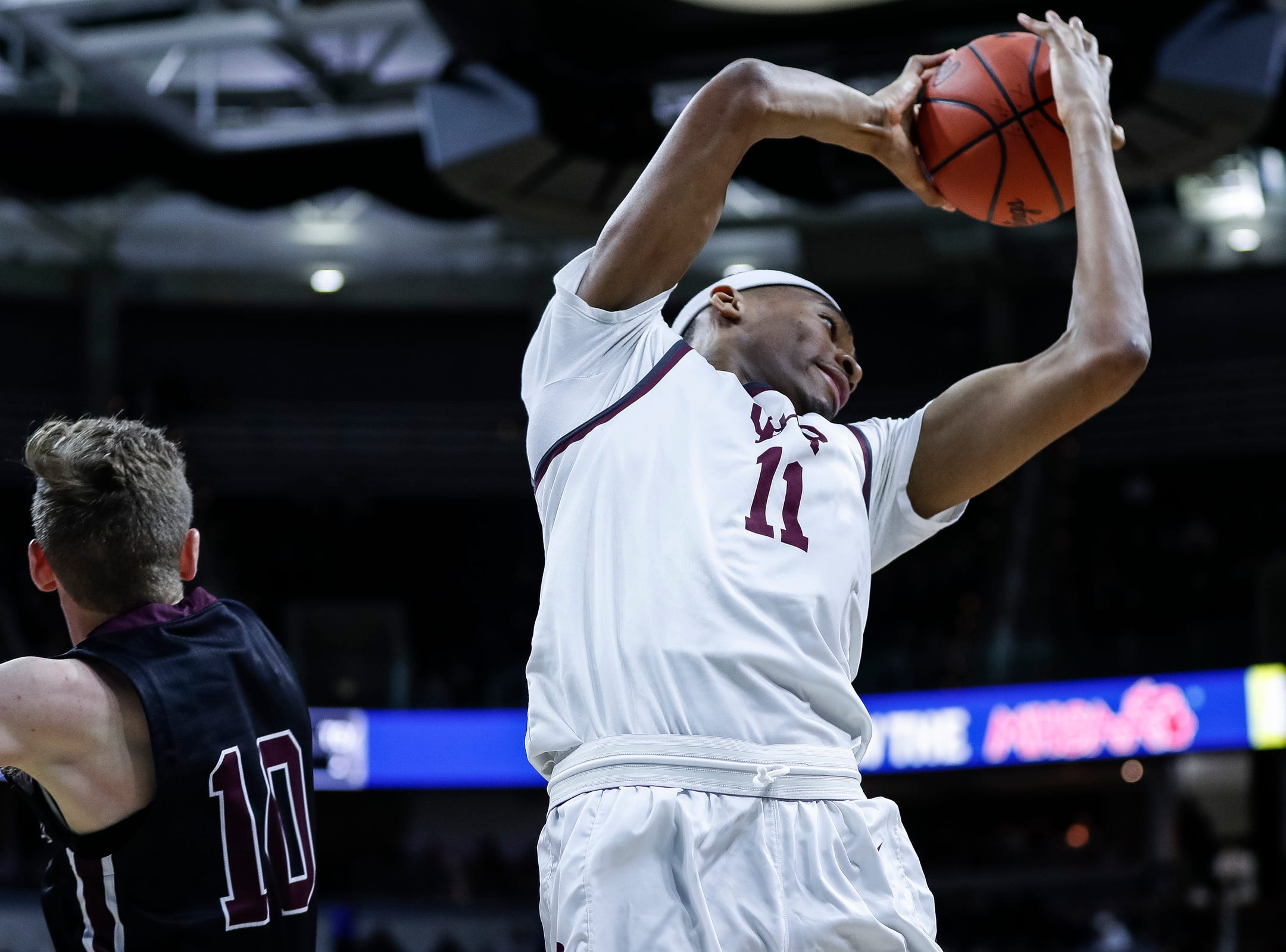 U-D Jesuit's Jalen Thomas (11) and Okemos' Zach Hetfield (10) battle for a rebound during the first half of MHSAA Division 1 semifinal at the Breslin Center in East Lansing, Friday, March 15, 2019.