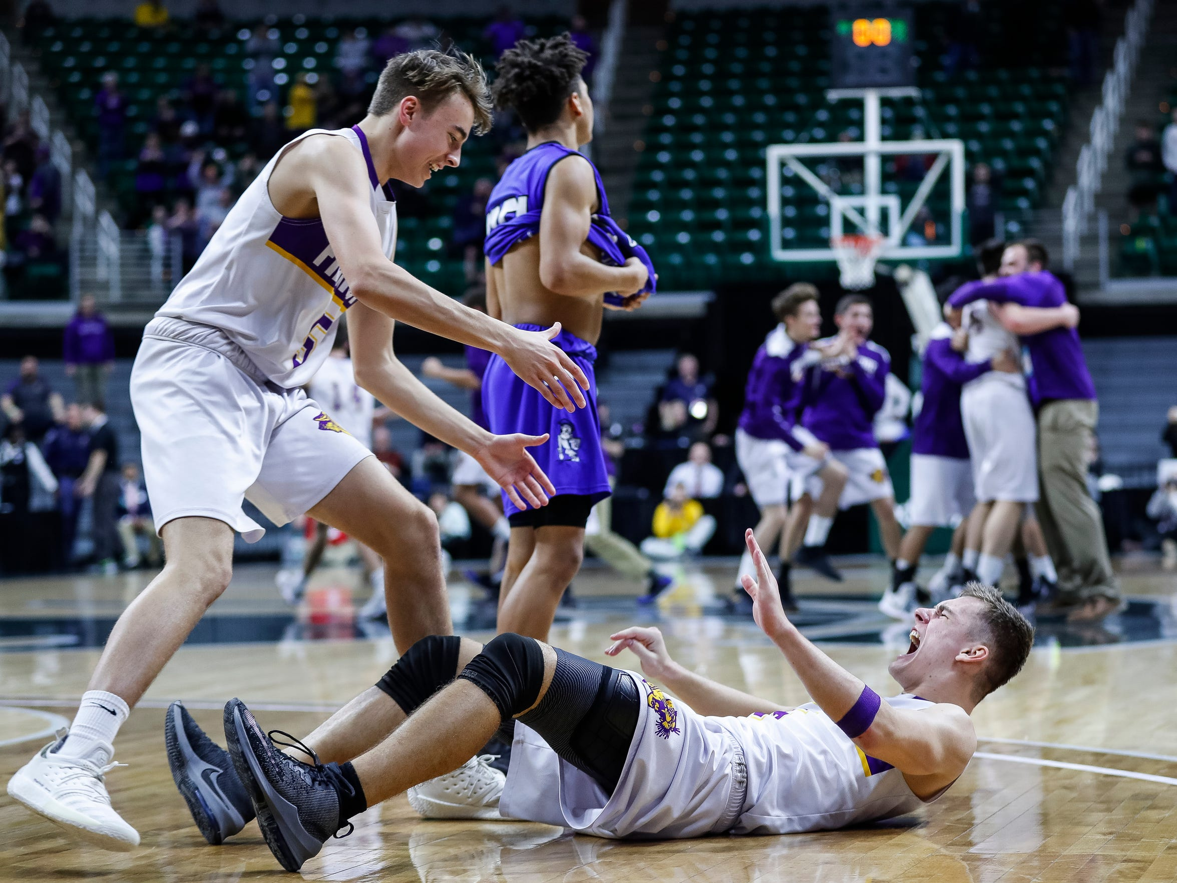 Frankfort's Luke Hammon (5) picks up his teammate Conner Smith (15) from the floor as they celebrate 44-43 win over Wyoming Tri-unity Christian during the second half of MHSAA Division 4 semifinal at the Breslin Center in East Lansing, Thursday, March 14, 2019.