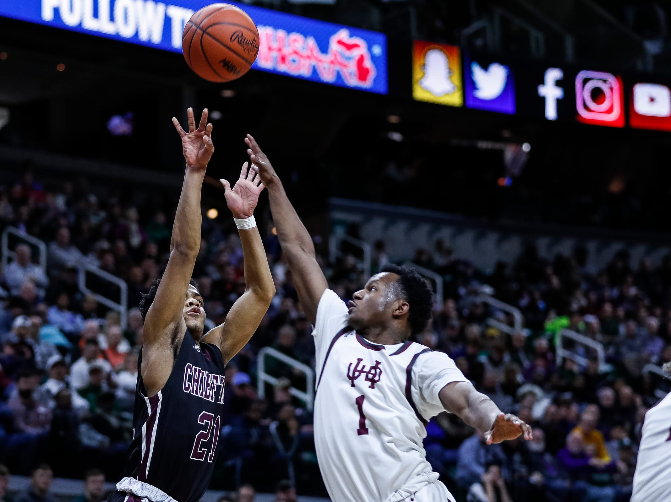 Okemos' Noah Pruitt (21) attempts for a 3-point basket against U-D Jesuit's Julian Dozier (1) during the first half of MHSAA Division 1 semifinal at the Breslin Center in East Lansing, Friday, March 15, 2019.