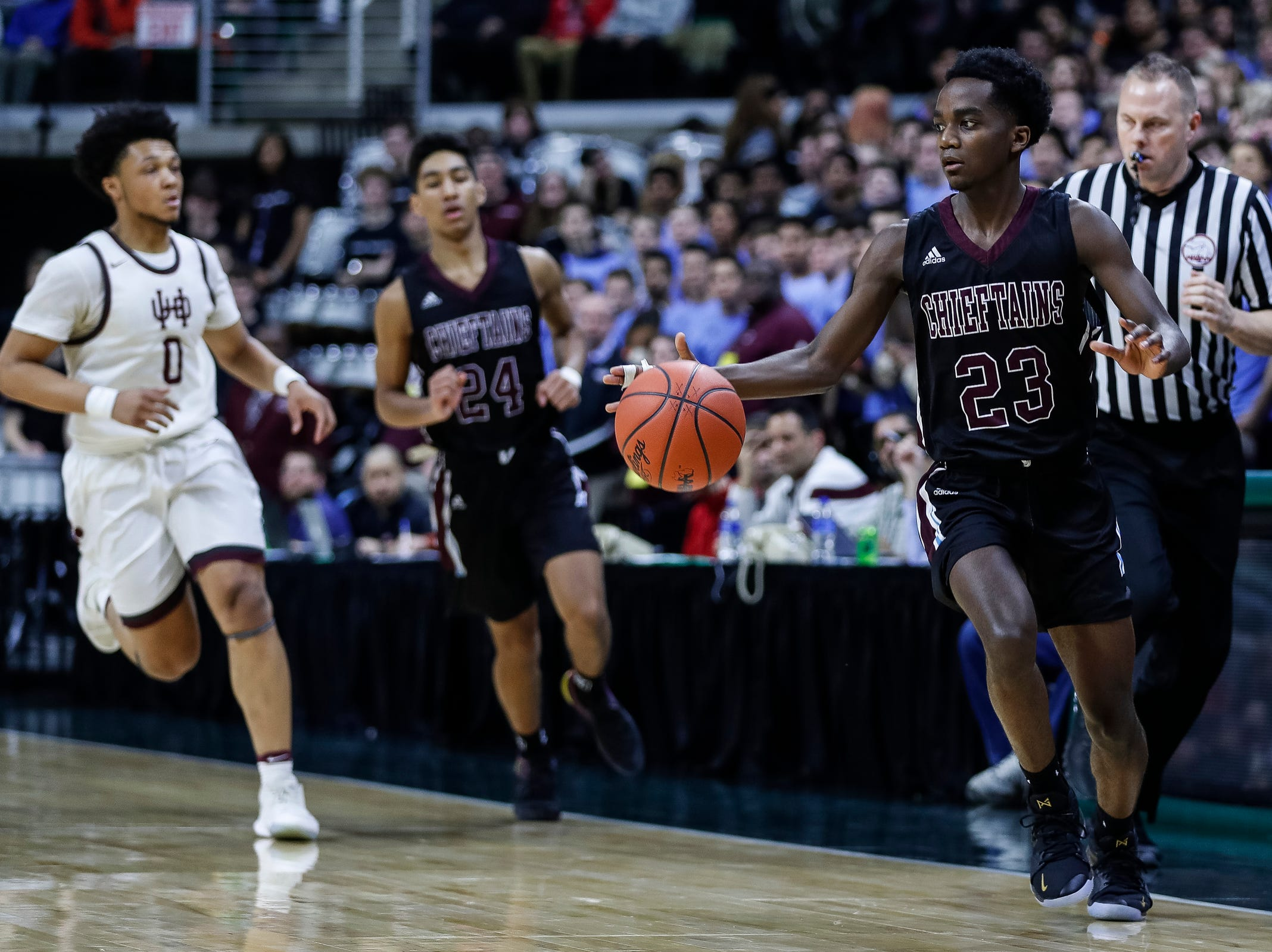 Okemos' Austin Gibson (23) dribbles against U-D Jesuit during the first half of MHSAA Division 1 semifinal at the Breslin Center in East Lansing, Friday, March 15, 2019.