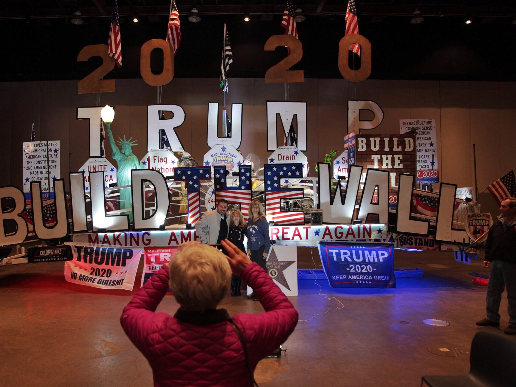 "Supporters take photos of a Trump display during Steve Bannon's nationwide tour stop named ""We Build the Wall"" in support Trump's wish for $7-billion expansion of border wall with Mexico, aimed at stopping illegal immigration on Thursday, March 14, 2019 at Cobo Center in downtown Detroit."