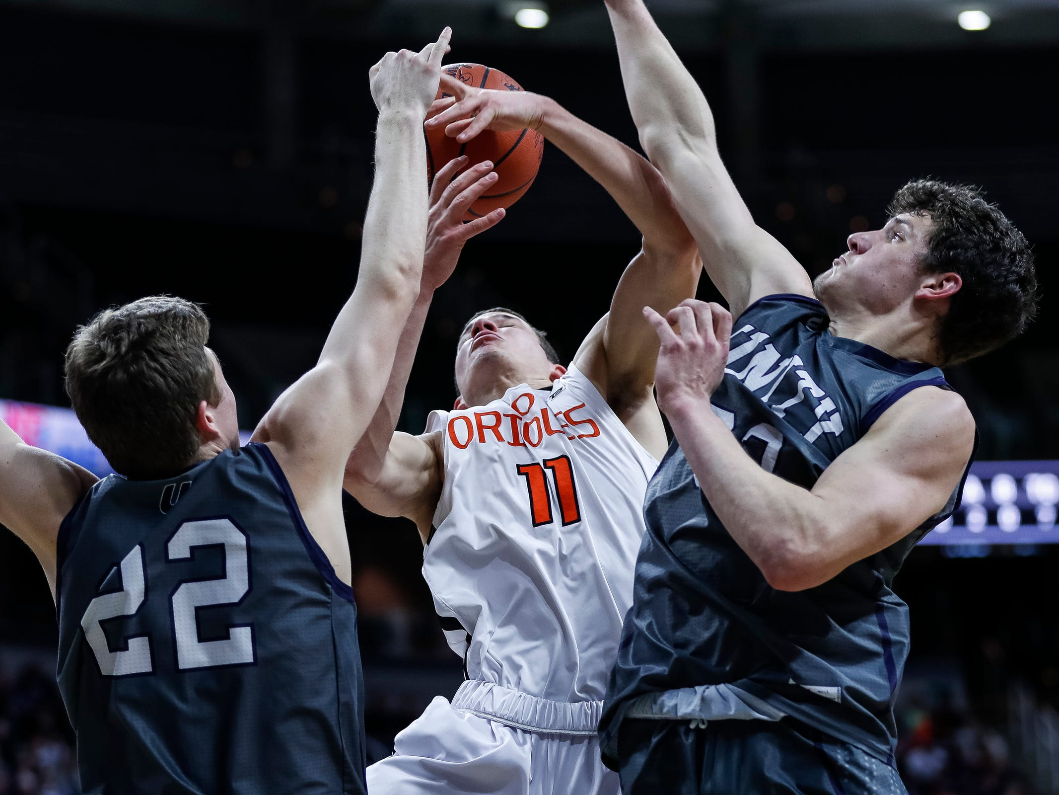Ludington's Joshua Laman (11) battles for a rebound with Hudsonville Unity Christian's Derek Slager (22) and T.J. VanKoevering (32) during the first half of MHSAA Division 2 semifinal at the Breslin Center in East Lansing, Friday, March 15, 2019.