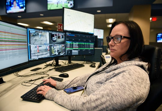 Breanna Lingo, 28, crime analyst, is seen monitoring her screens inside the Real-Time Crime Center at the Detroit Public Safety headquarters .