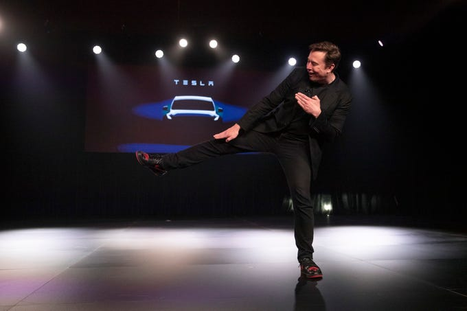 Tesla CEO Elon Musk jokingly kicks before introducing the Model Y at Tesla's design studio Thursday, March 14, 2019, in Hawthorne, Calif. The Model Y may be Tesla's most important product yet as it attempts to expand into the mainstream and generate enough cash to repay massive debts that threaten to topple the Palo Alto, Calif., company.