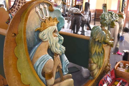 Poseidon, Greek god of the sea, brandishes his trident on one of the bench-seats on the carousel.