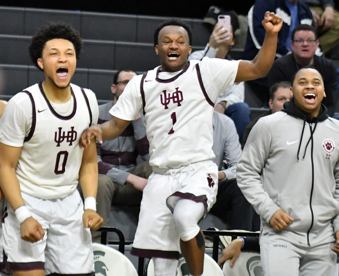 U-D Jesuit's Daniel Friday (0) and Julian Dozier (1) react from the bench while watching younger players getting a chance to play in the second half of the Cubs' Div. 1 semifinal victory over Okemos 63-25.