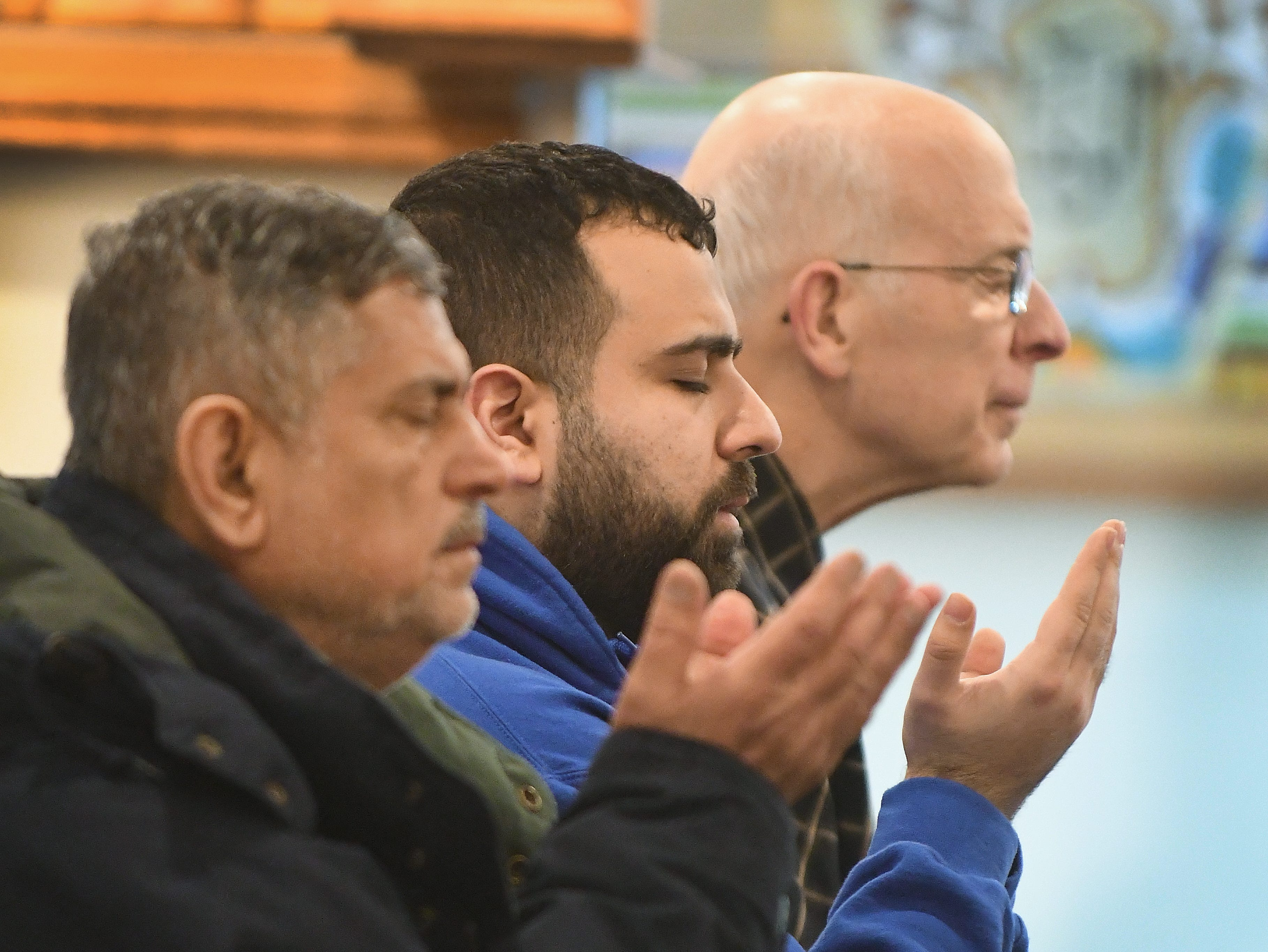 Ibrahim Alhaddad and Hamze Zein are joined by David Kasbow from Metro Detroit Family Church at a prayer service at the Islamic House of Wisdom in Dearborn Heights Friday.