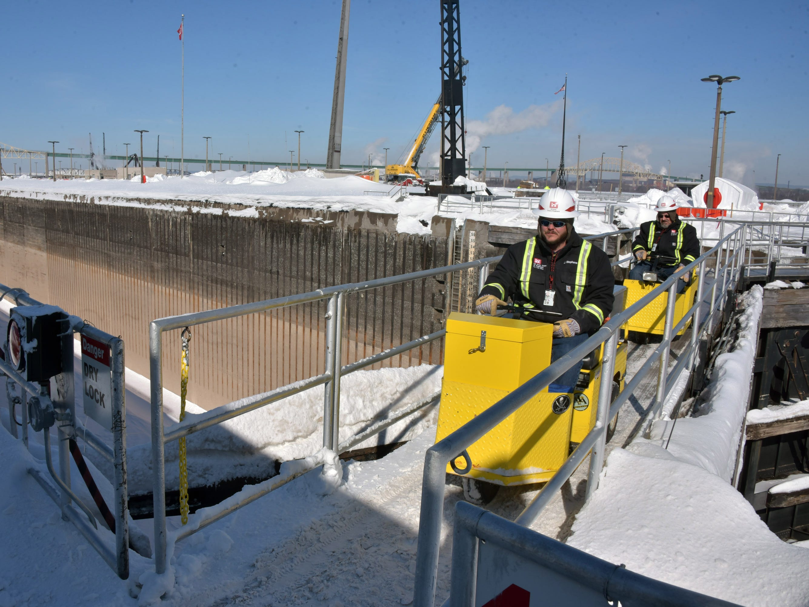 Two U.S. Corps of Engineers workmen drive scooters across a gate at the MacArthur Lock in Sault Ste. Marie. The electric scooters are used to move around the huge complex.