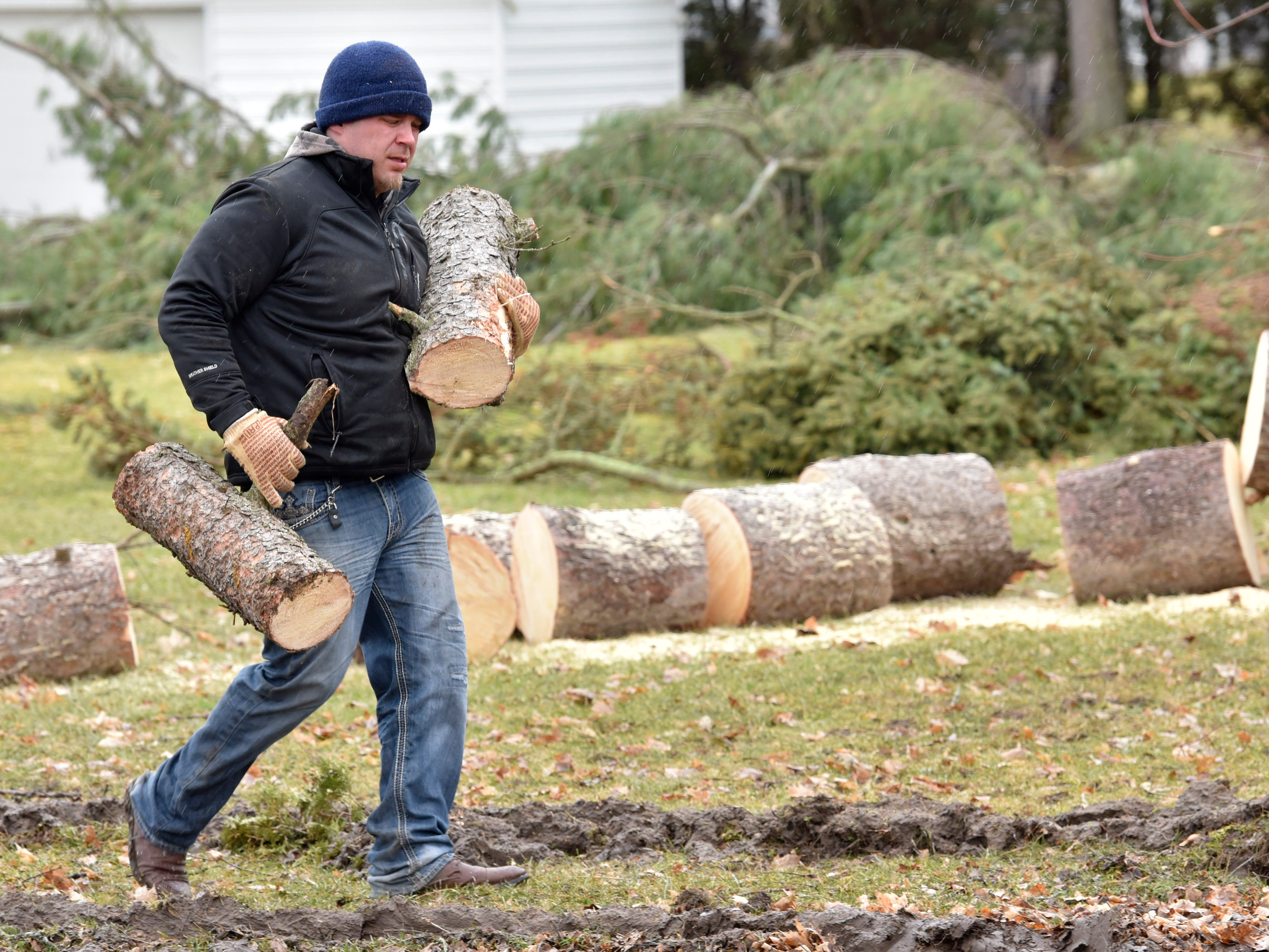 This man carries logs to a waiting truck as community members cut up trees in a yard along Newburg Rd. near Foundry Rd. in Vernon Twp.
