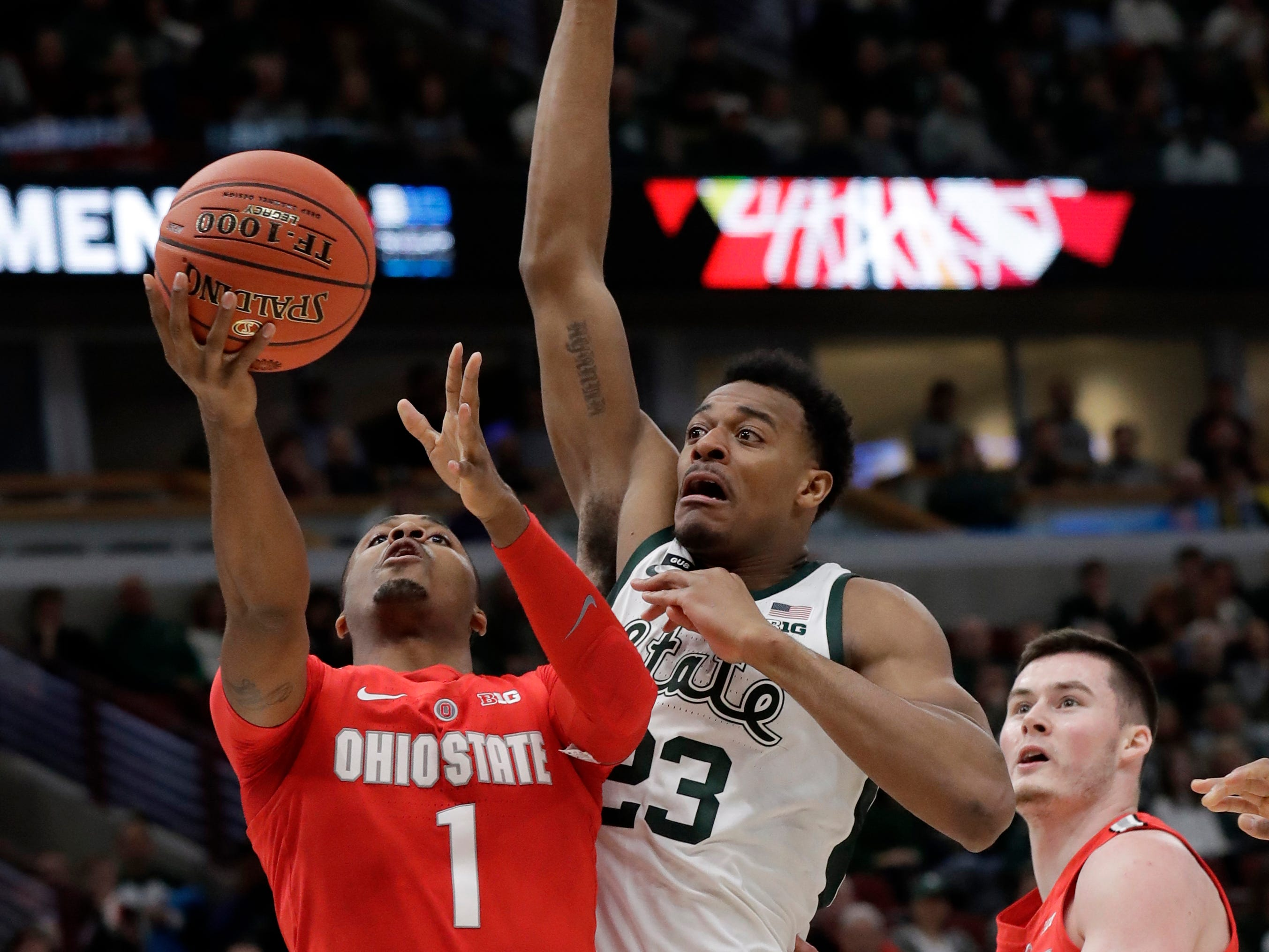 Ohio State's Luther Muhammad (1) takes a shot against Michigan State's Xavier Tillman (23) during the first half.