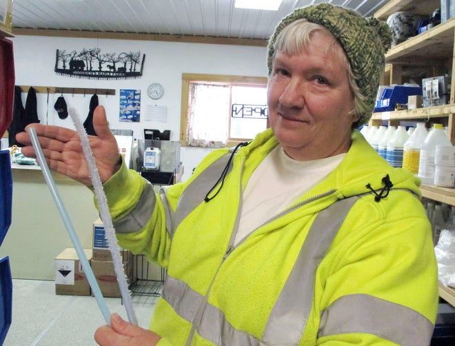 Ruth Goodrich of Goodrich's Maple Farm in Danville, Vt., holds squirrel-damaged maple sap tubing, right, and new tubing, left, in the farm's equipment shop.