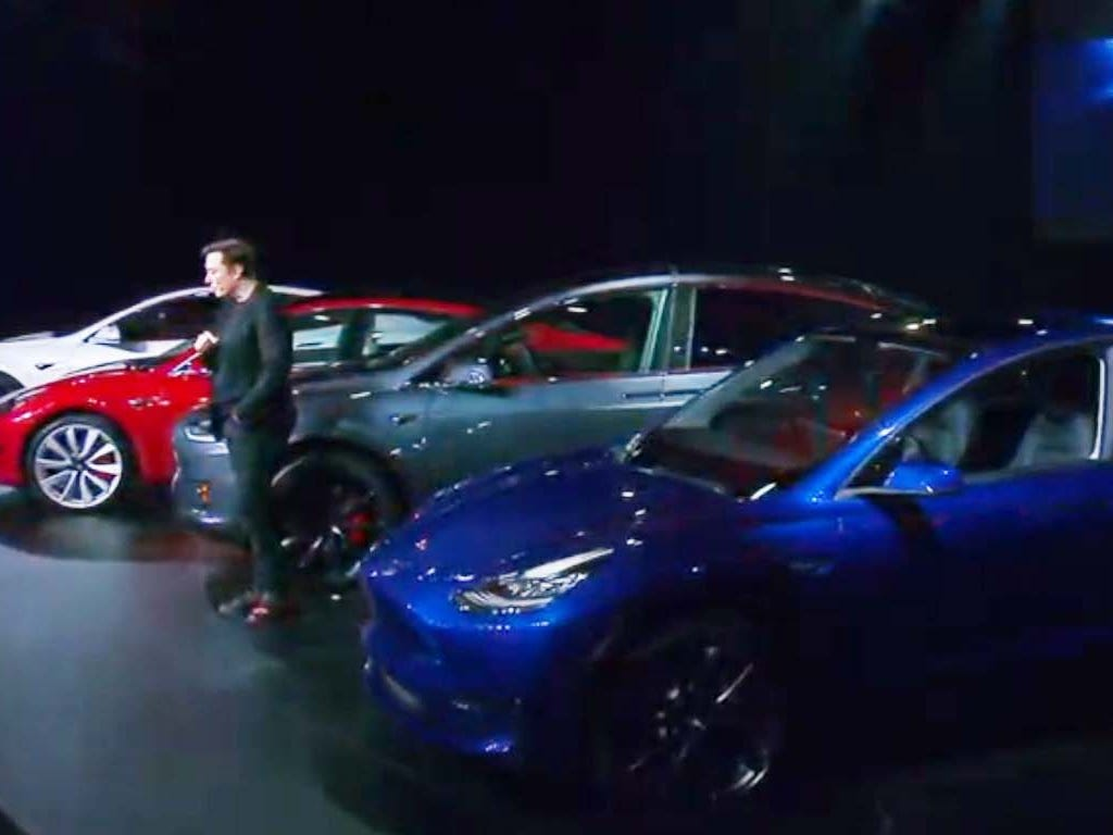 """Tesla CEO Elon Musk with his """"S3XY"""" lineup of EVs: (from left) Model S, MOdel 3, Model X, and Model Y. """"We are bringing sexy back!"""" reveled Musk at his LA news conference."""