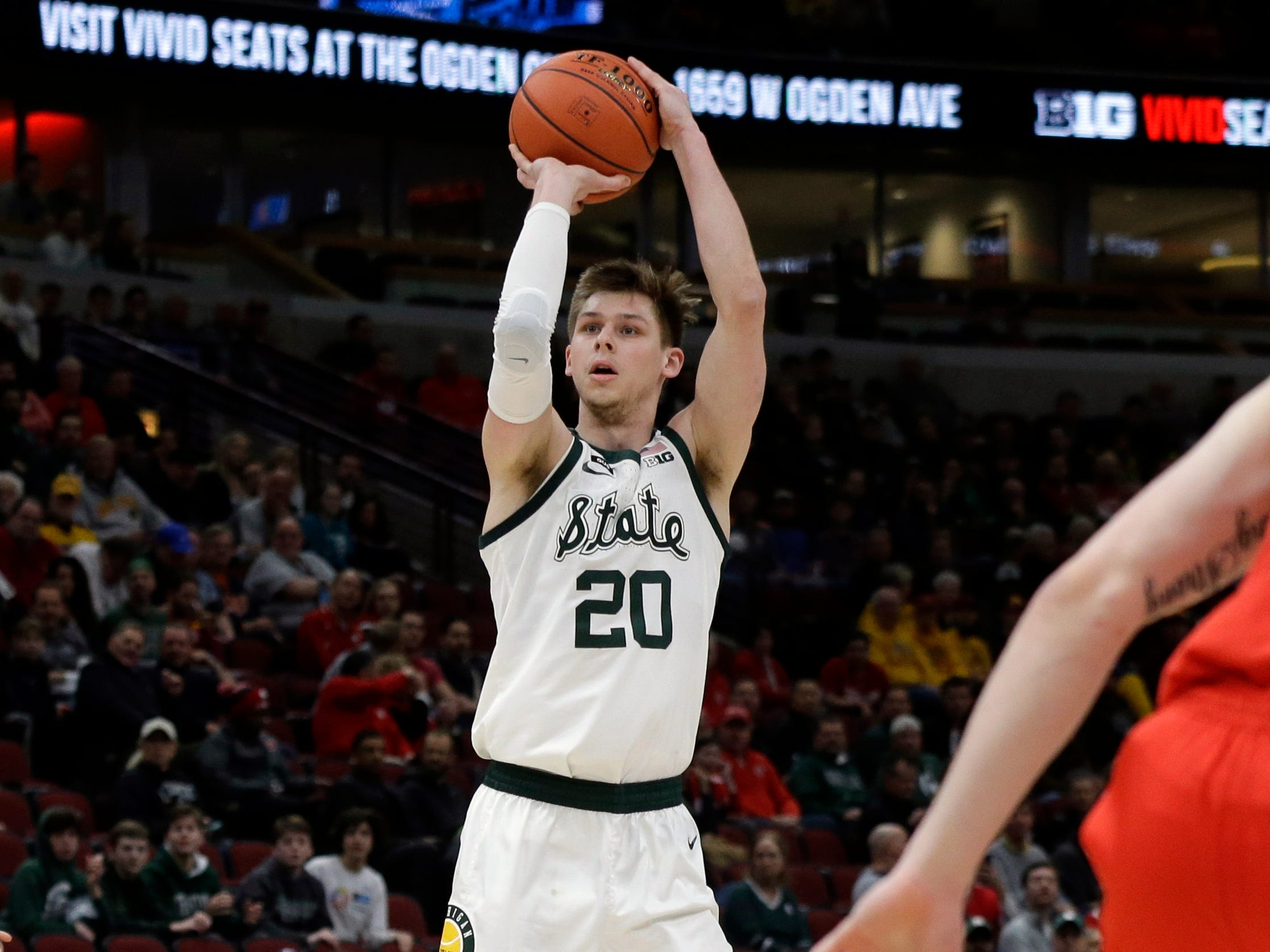 Michigan State's Matt McQuaid (20) shoots during the first half.
