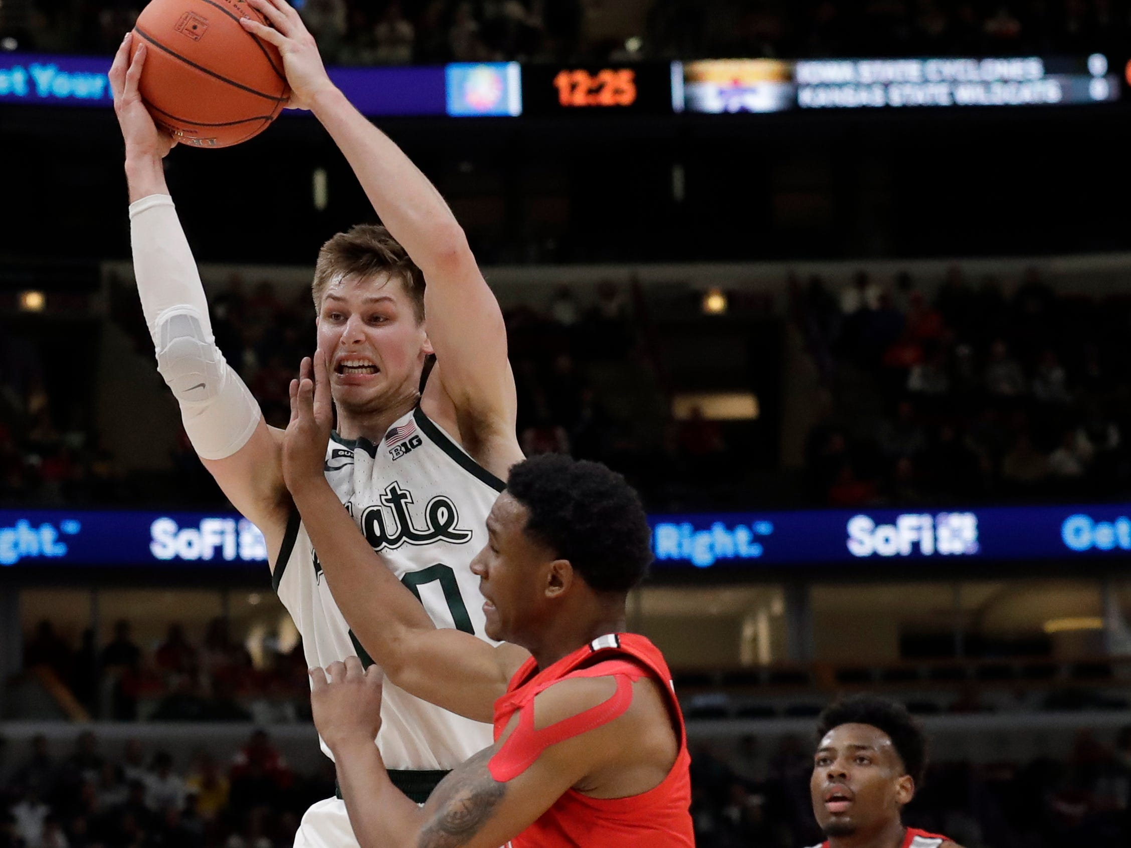 Michigan State's Matt McQuaid (20) grads a rebound against Ohio State's C.J. Jackson (3) during the first half.