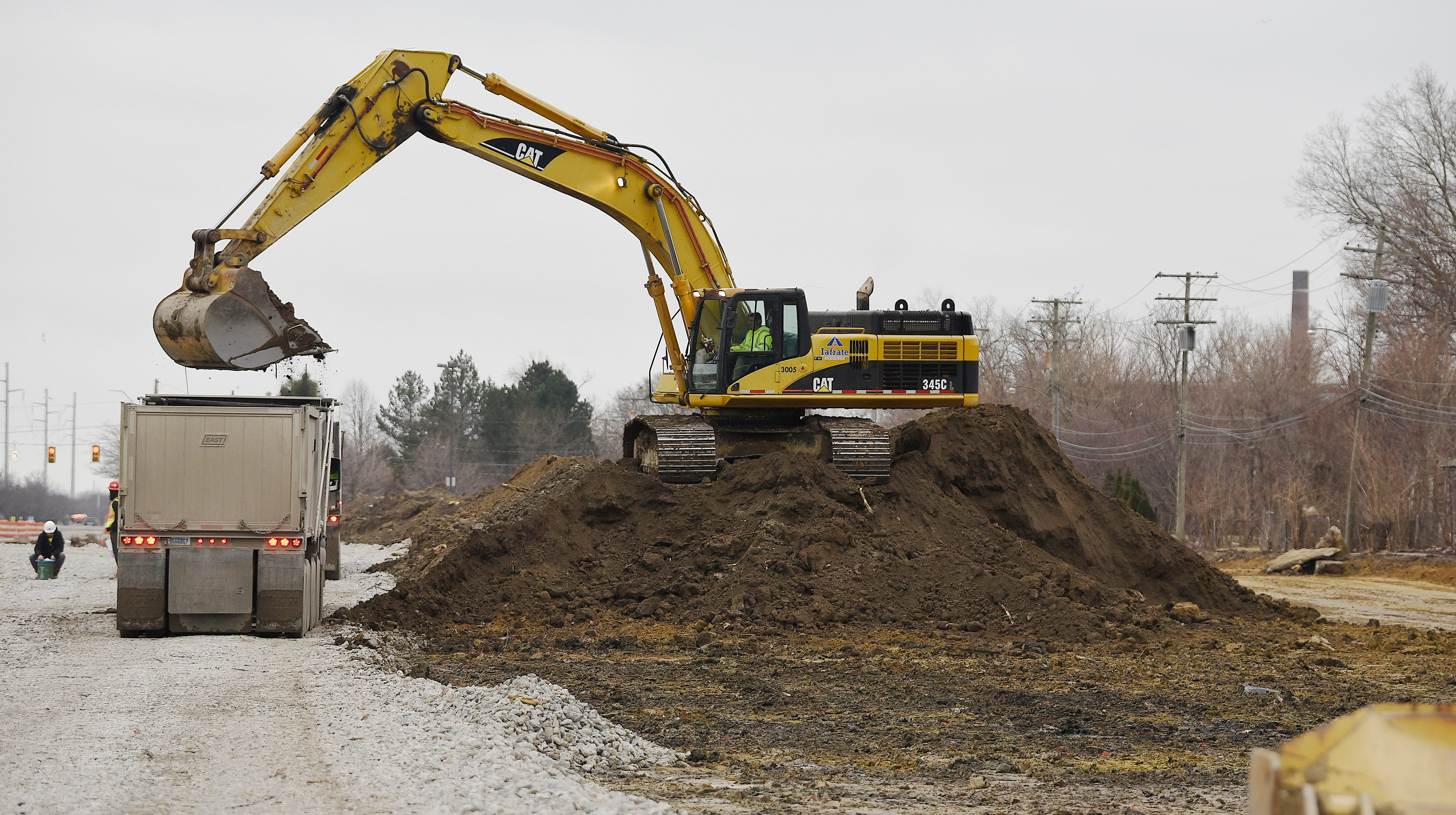 A operator from Iafrate Construction Co. uses an excavator to remove soil from land on St. Jean near E. Canfield in Detroit, Friday, March 15. The land is part of the 200 acres that the city needs to acquire for the proposed Fiat Chrysler Mack Avenue Assembly complex.