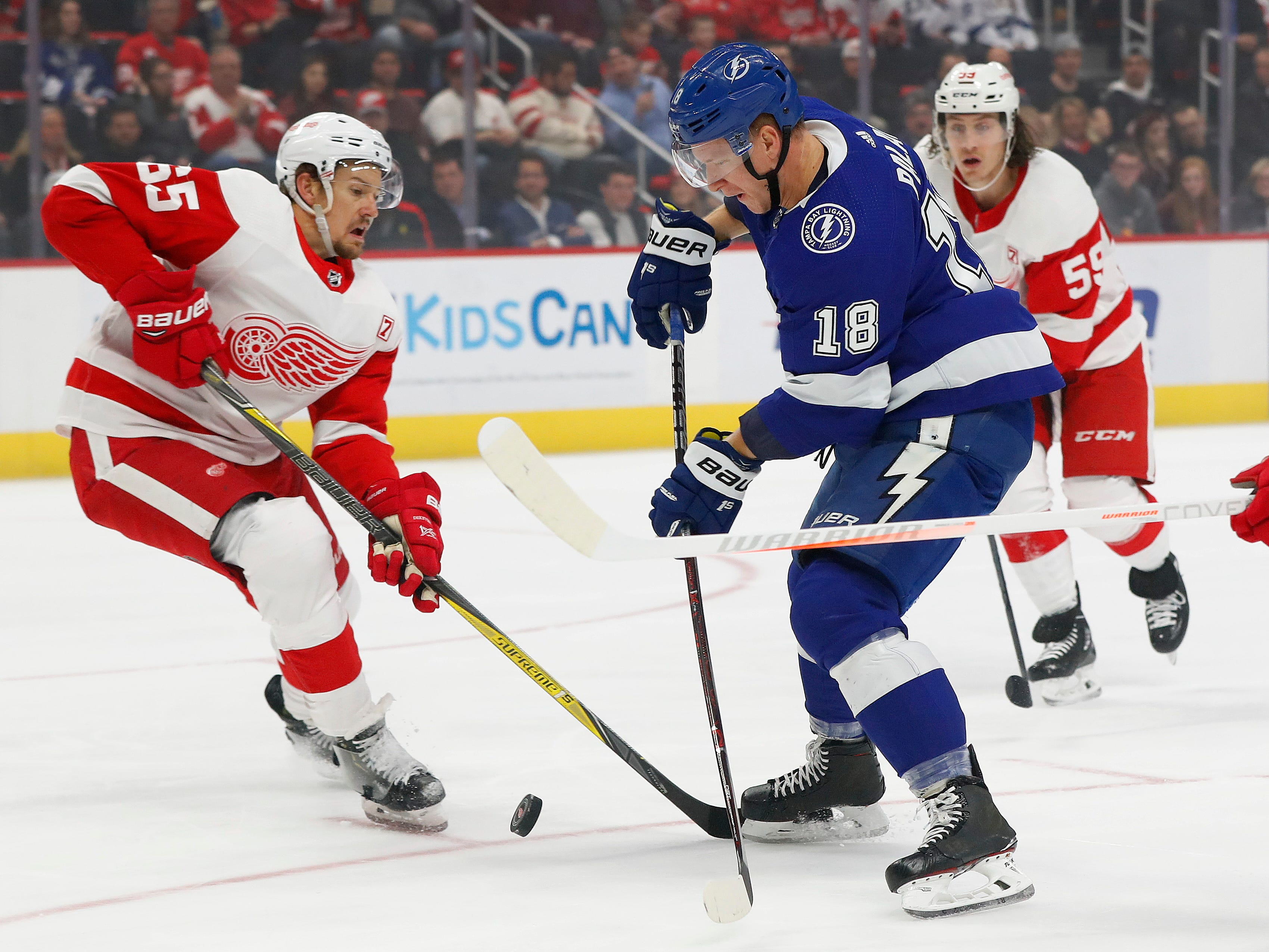 Tampa Bay Lightning left wing Ondrej Palat (18) shoots on Detroit Red Wings defenseman Danny DeKeyser (65) in the first period onThursday, March 14, 2019, in Detroit, Michigan.