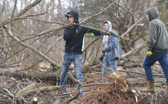 People cut up trees along Newburg Road at Foundry Road in Vernon Township.