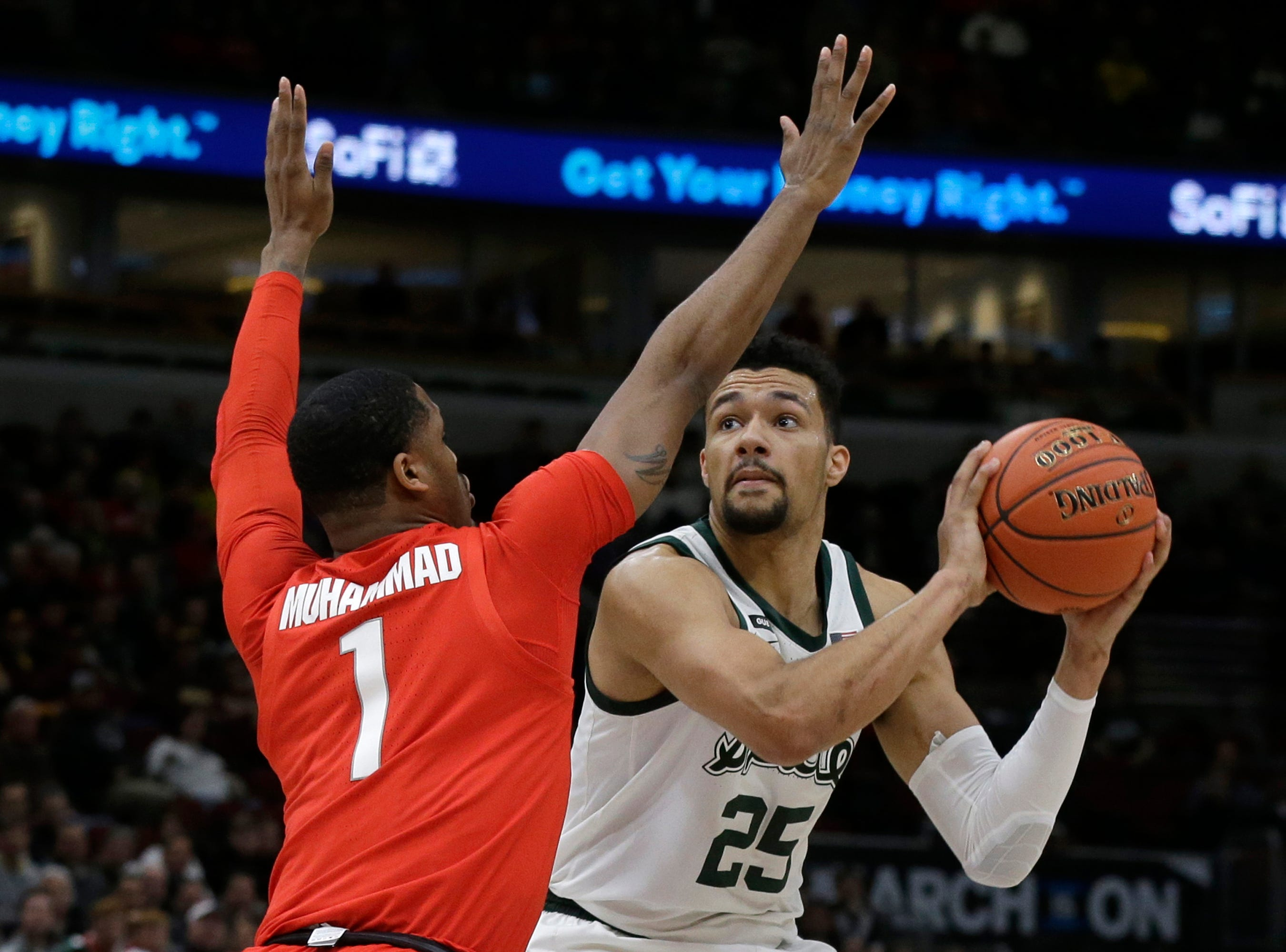 Michigan State's Kenny Goins (25) drives against Ohio State's Luther Muhammad (1) during the first half.