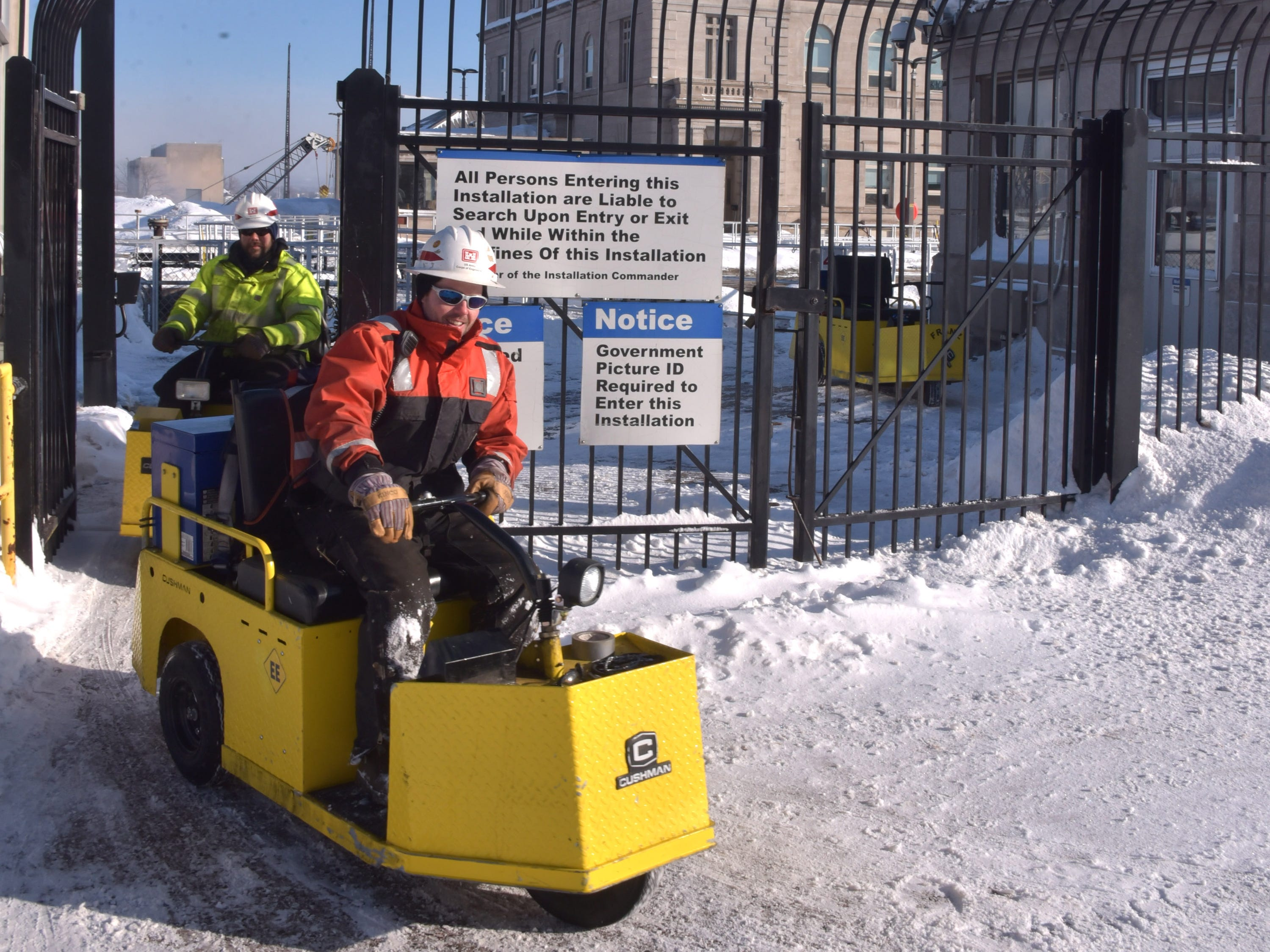 Two U.S. Army Corps of Engineers workers use small electric carts to move around the huge Soo Locks complex.