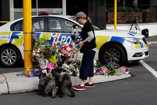 A women places flowers at a makeshift memorial near the Masjid Al Noor mosque in Christchurch, New Zealand, Saturday, March 16, 2019, where one of the mass shootings occurred yesterday.
