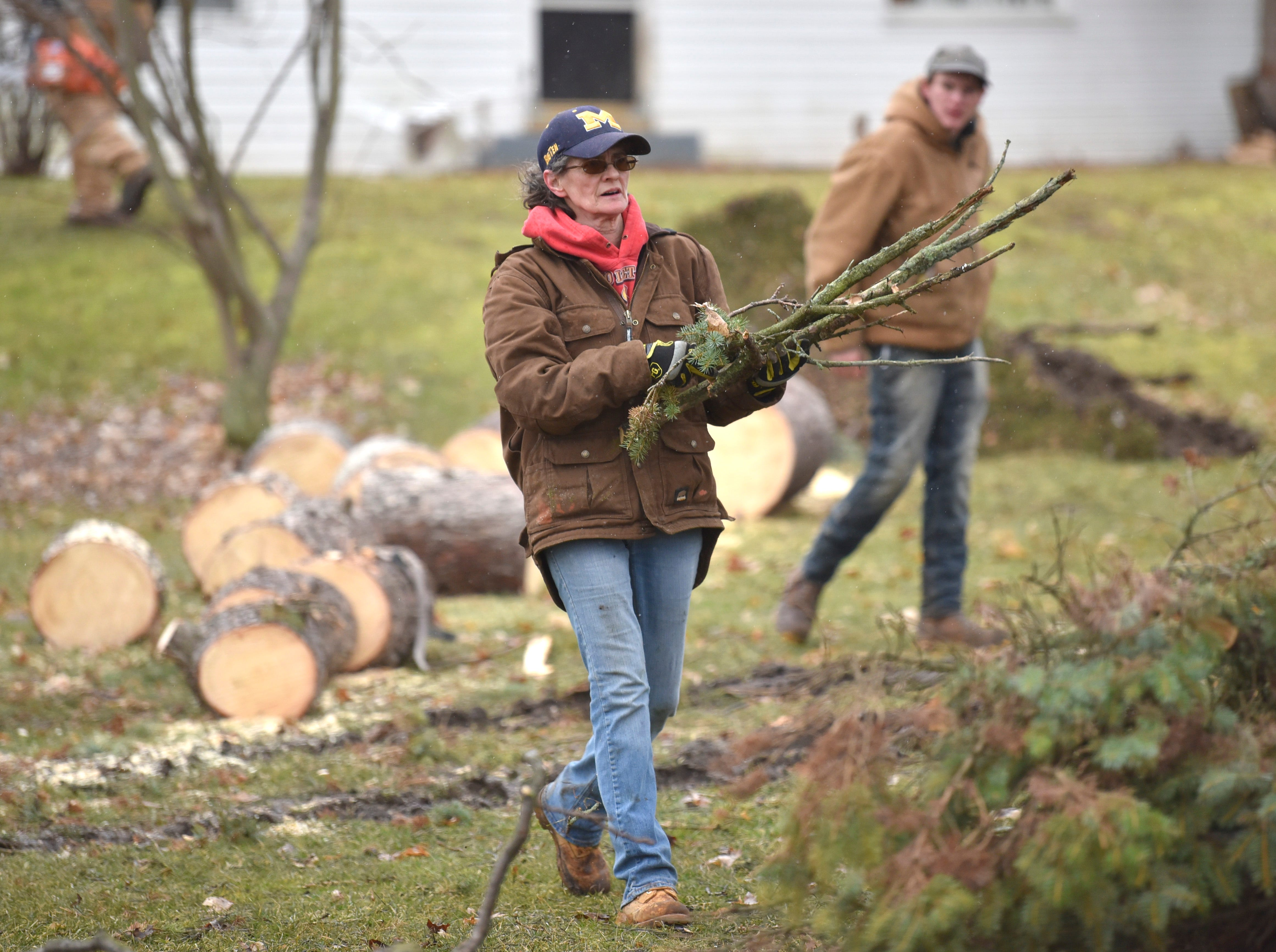 This woman stacks up brush as family members and friends cut up trees in this yard along Newburg Rd. near Foundry Rd. in Vernon Twp.