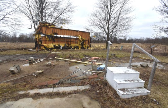 The steps stayed in place, but this mobile home in Mount Morris in Genesee County was lifted off its foundation and wrapped around a tree, with debris extending into an adjacent field.