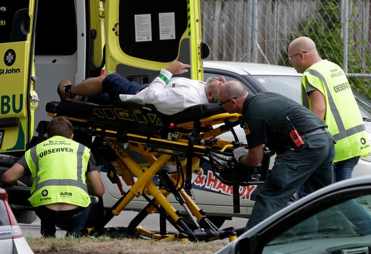 "Ambulance staff take a man from outside a mosque in central Christchurch, New Zealand, Friday.  At least 49 were killed in shootings at two mosques full of worshipers at Friday prayers on what the prime minister called ""one of New Zealand's darkest days,"" as authorities detained four people and defused explosive devices in what appeared to be a carefully planned attack."