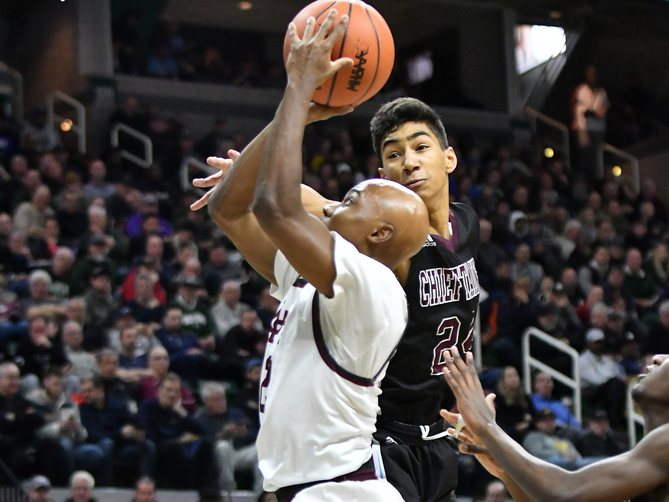 Okemos's Evan Thomas defends a shot by U-D Jesuit's Caleb Hunter (2) in the first half.