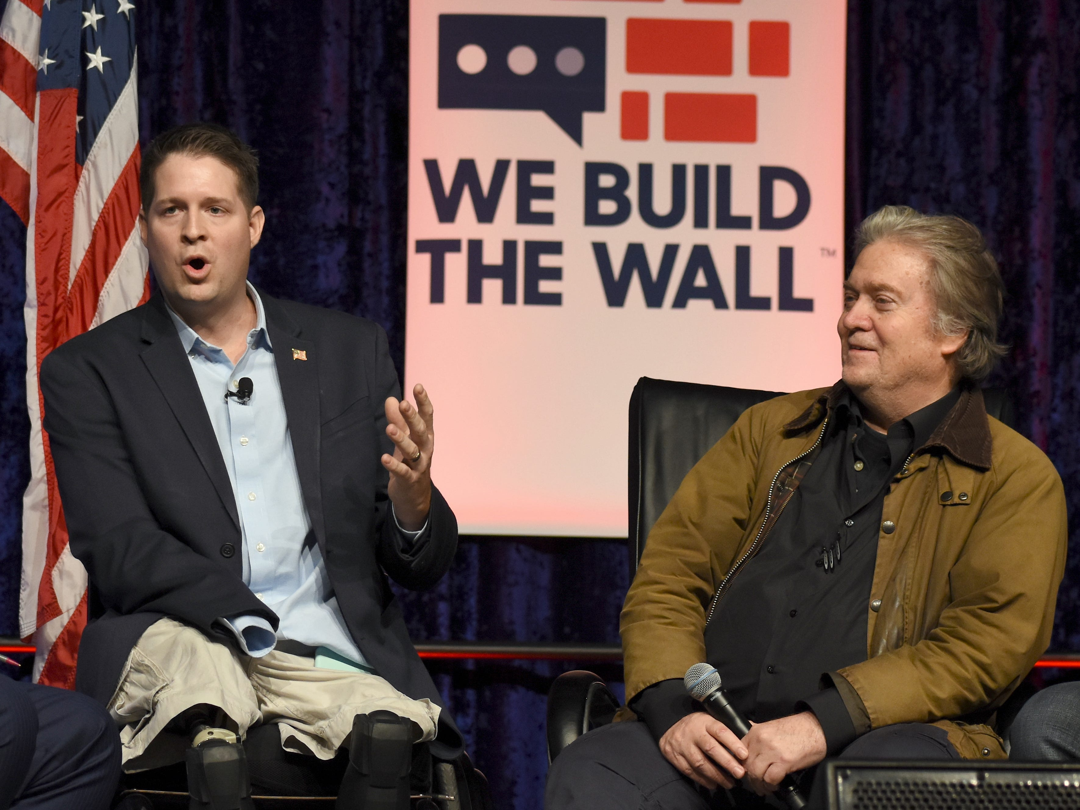 "Several hundred supporters gather to listen to speakers like former White House chief strategist Steve Bannon and Brian Kolfage, left, a triple amputee veteran who organized a private fundraising campaign to finance the border wall, at a ""We Build The Wall"" town hall meeting at Cobo Center in Detroit, Michigan on March 14, 2019."