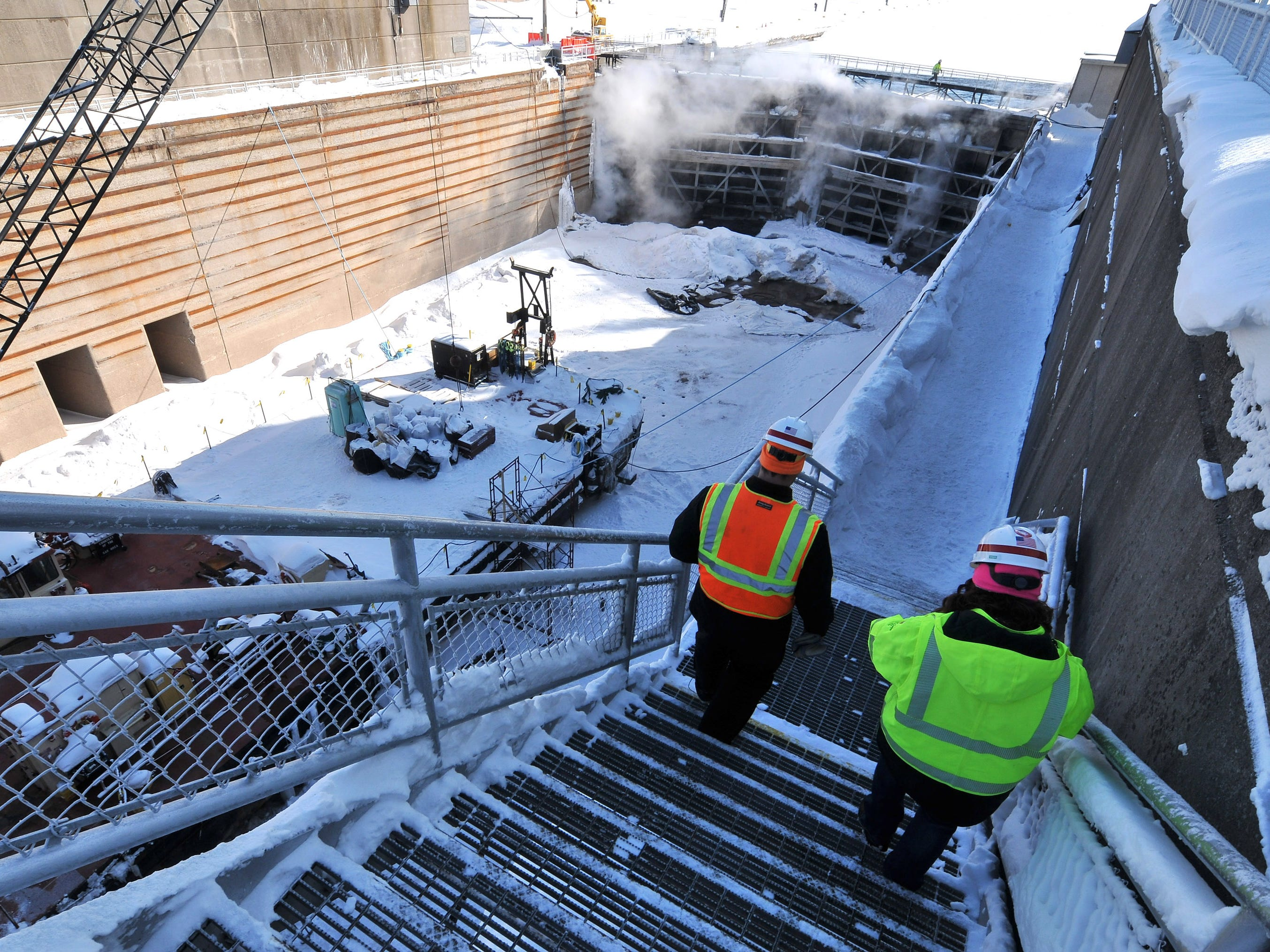 U.S. Corps of Engineers chief of maintenance Jeff Harrington, left, and chief of operations LeighAnn Ryckeghen walk down into the Poe Lock Tuesday, March 12, 2019.