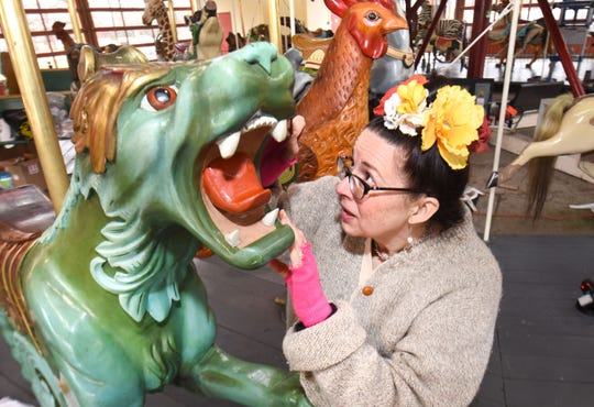 Where necessary, the wooden animals on Greenfield Village's carousel get a little dental work from the artist.