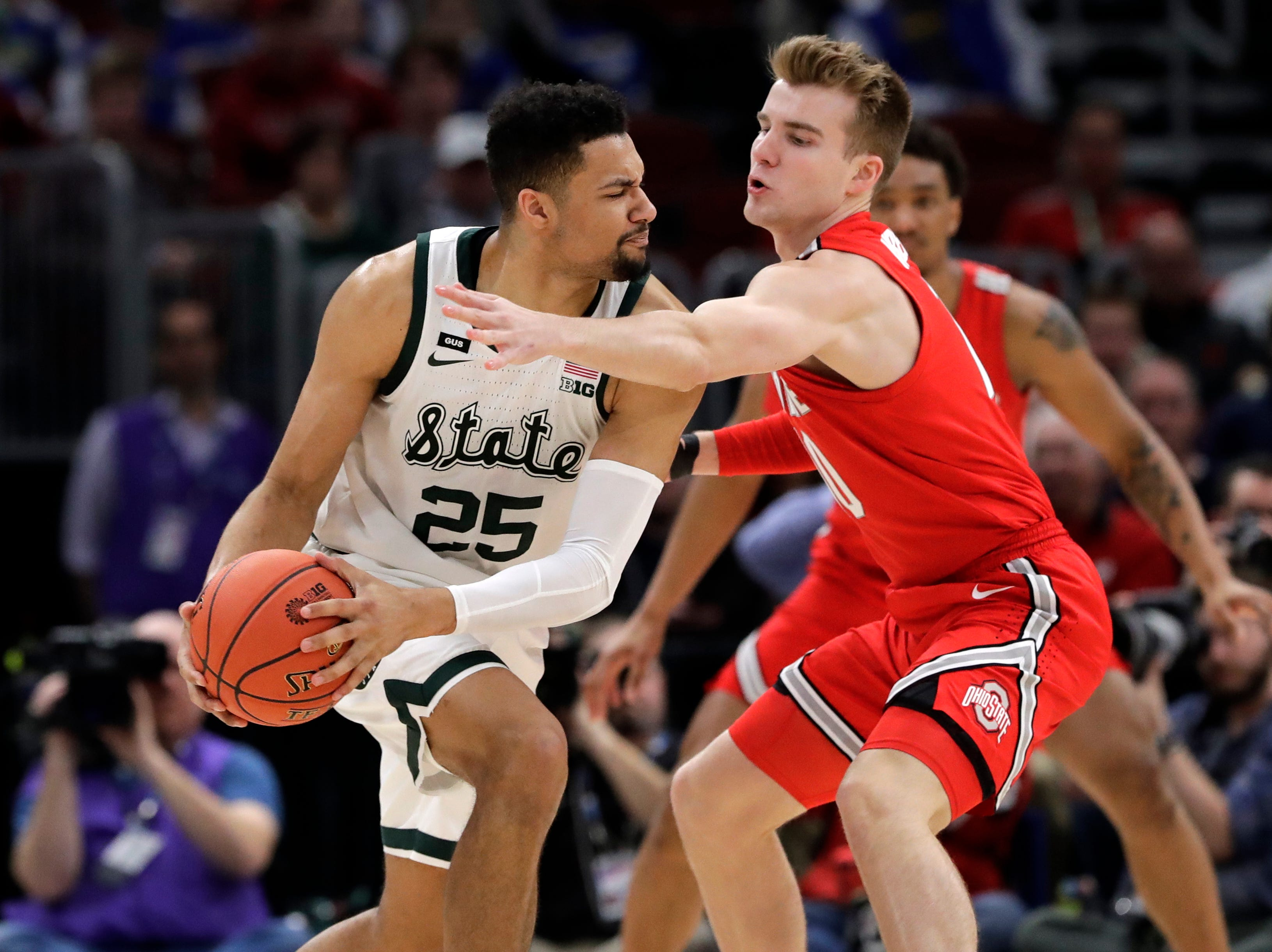 Michigan State's Kenny Goins (25) looks to pass the ball against Ohio State's Justin Ahrens during the first half.