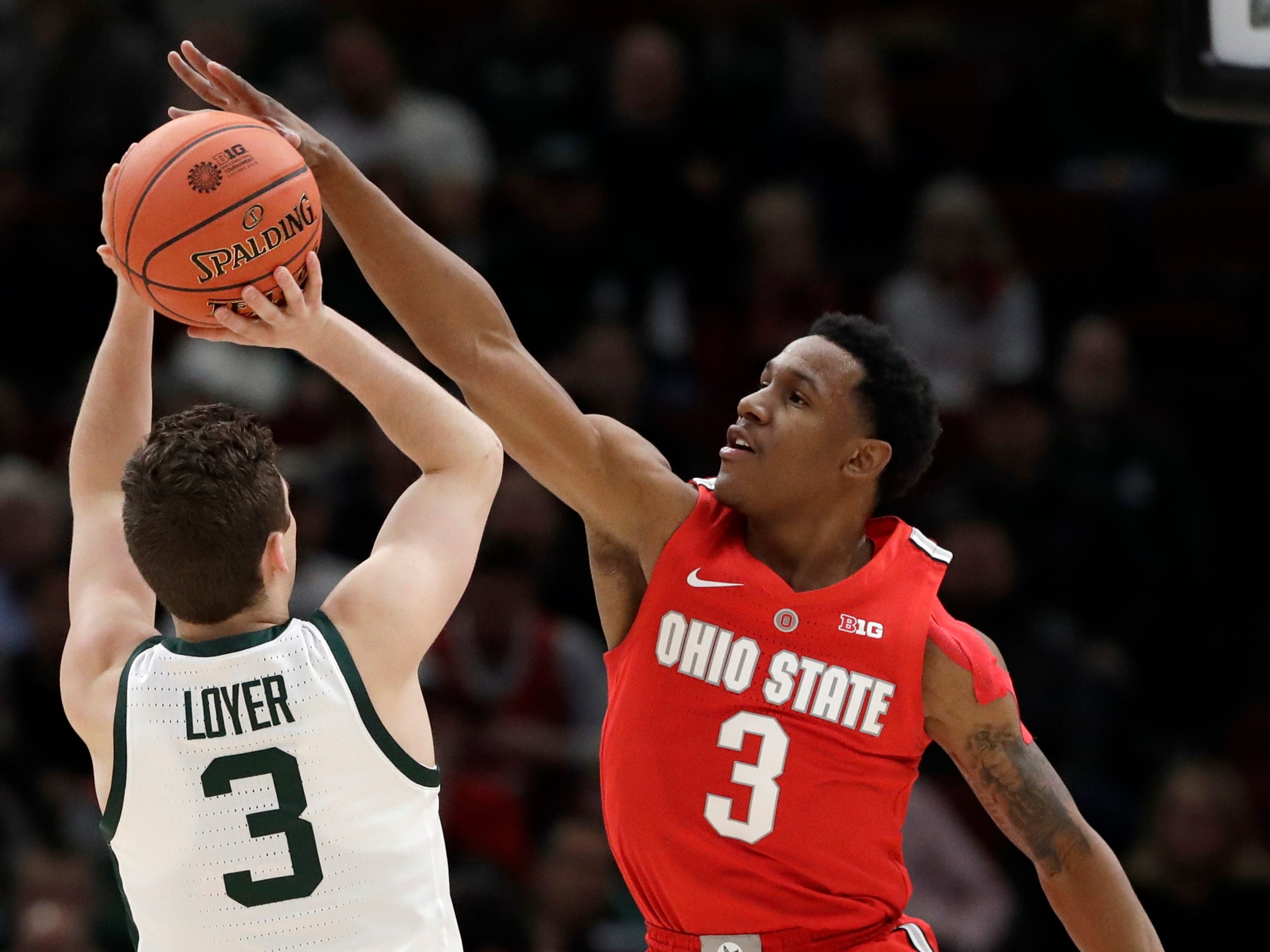 Ohio State's C.J. Jackson, right, blocks a shot by Michigan State's Foster Loyer during the first half.