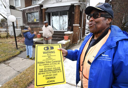 James Jackson of Detroit, 70, shows off a sign that residents are allowed to post around the neighborhood, advising that cameras are present.  Jackson, as well as neighbors Audrey Carter and Harry Jolliffi, behind him, have cameras on their houses for protection.