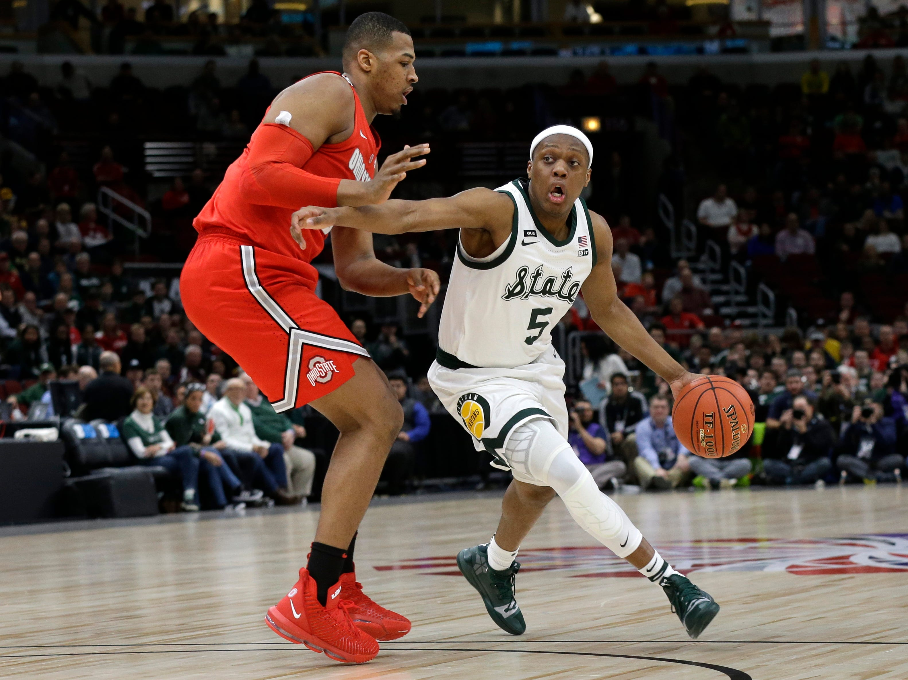Michigan State's Cassius Winston (5) drives against Ohio State's Kaleb Wesson during the first half.