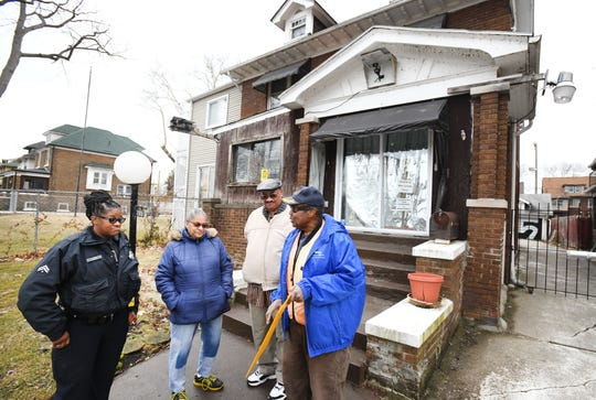 Detroit neighborhood police officer Karen Maxey stops and visits with James Jackson, right, and neighbors Audrey Carter and Harry Jolliffi, as they discuss the cameras they have on their homes for protection in Detroit, Michigan on March 15, 2019.  (Image by Daniel Mears / The Detroit News)