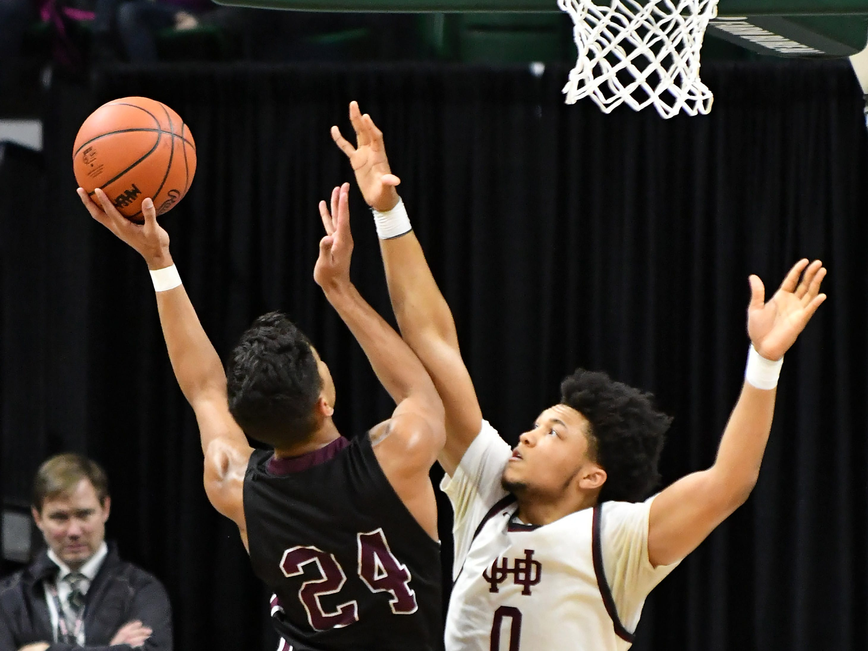 U-D Jesuit's Daniel Friday (0) defends a shot by Okemos's Evan Thomas (24) in the first half.