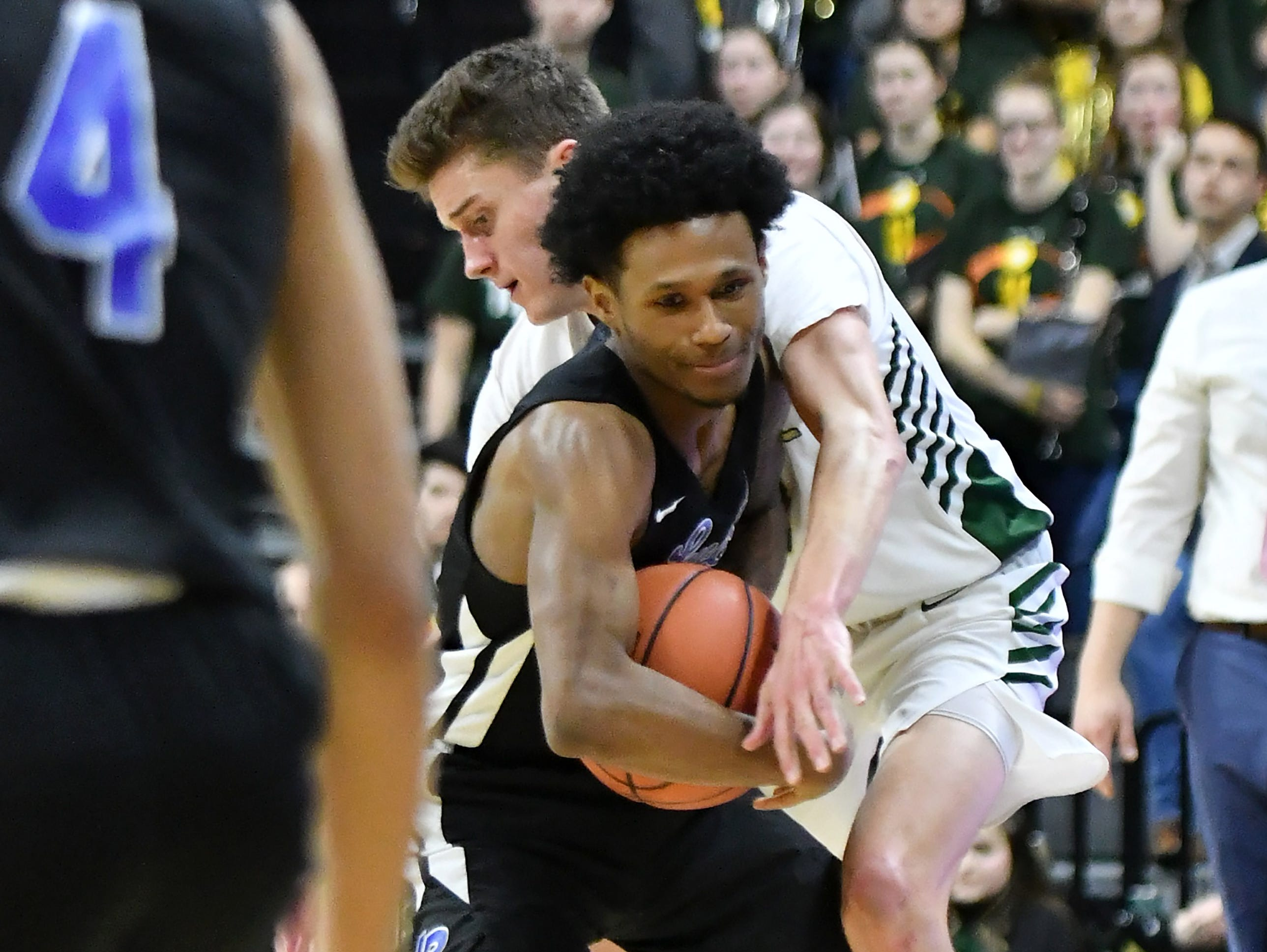 Howell's Kip French tries to steal the ball from Lincoln guard Jalen Fisher (14)  in the second half.