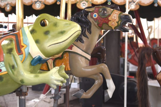 A frog and horse race one another on the historic 1913 carousel at The Henry Ford.