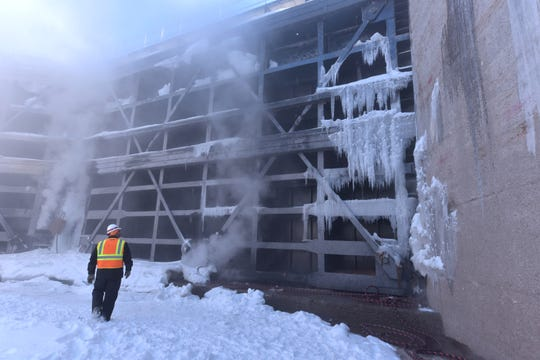 Steam rises against a water gate in the Poe Lock as U.S. Corps of Engineers' Jeff Harrington  inspects the ice cover. Steam is used to remove ice and snow from the dewatered lock, which has been without water for a 10-week winter maintenance and repair schedule.