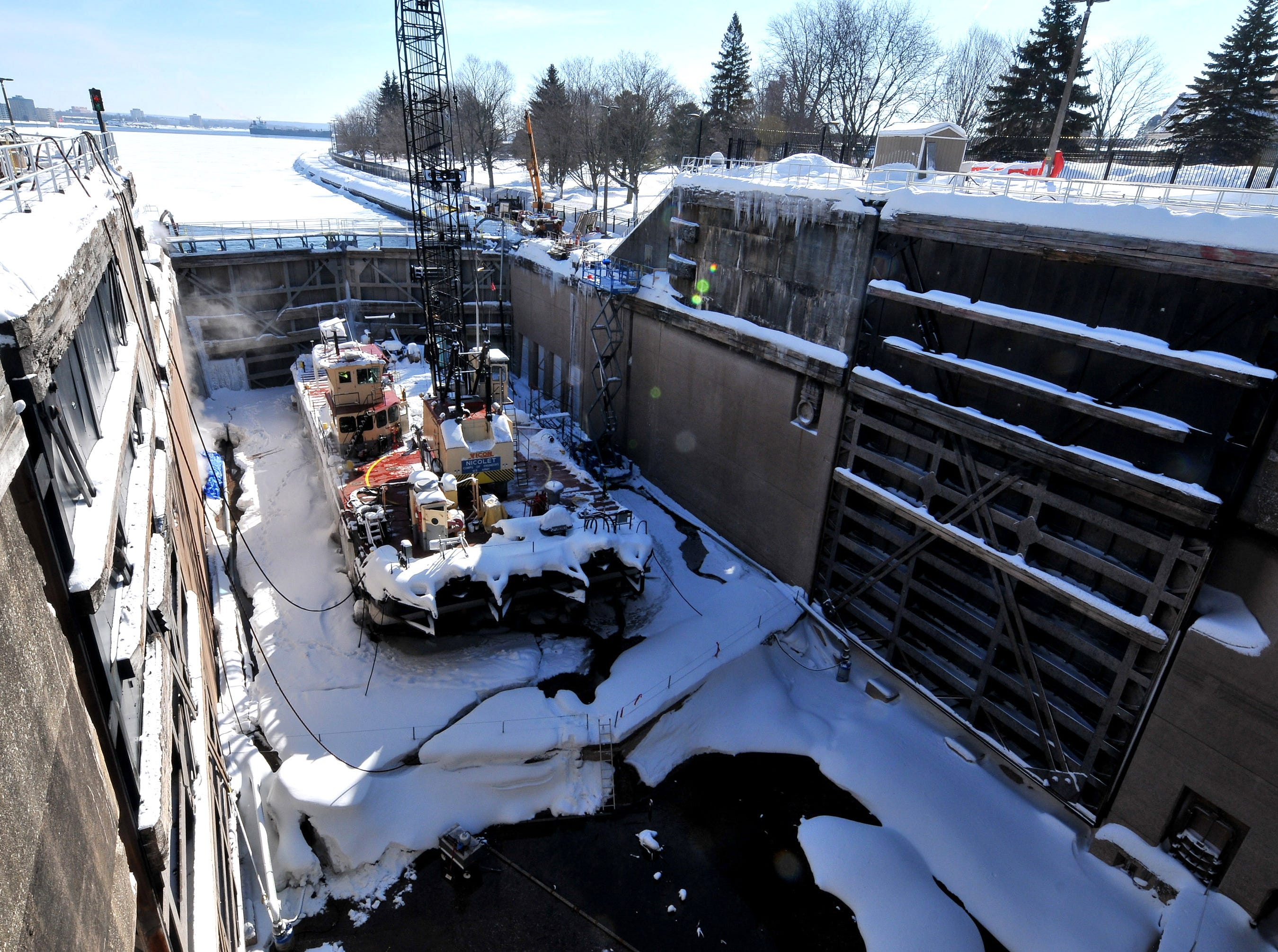 A winter maintenance work barge sits in the bottom of the MacArthur Lock Tuesday, March 12, 2019 in Sault Ste. Marie, Mich. A crane and other equipment were used for maintenance and repair over a 10-week shutdown of the facility. When water is added to the lock, the barge will be floated out to allow shipping to pass through.