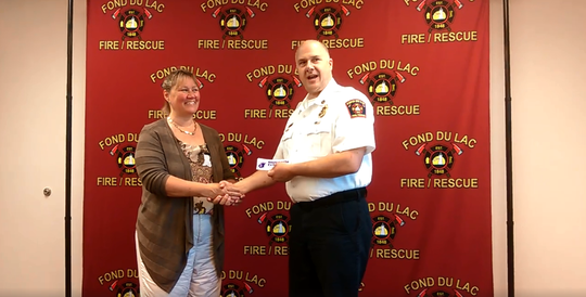 Cathy Loomans of the Fond du Lac County Dementia Friendly Task Force presents a purple angel window cling to FDL Fire and Rescue Assistant Chief of EMS Todd Janquart following the completion of the FDL Fire and Rescue's training.
