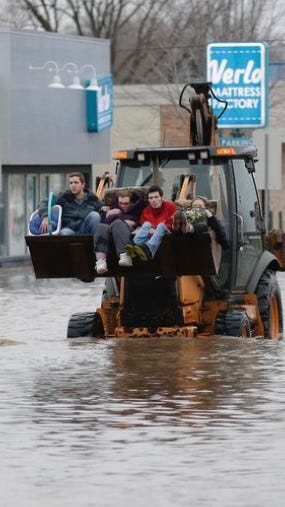 Linda Patt, second from left, is driven to safety in the bucket of a front end loader Thursday, March 14, 2019, as she was rescued from flooded Georgetown Cleaners at 441 W. Johnson St.