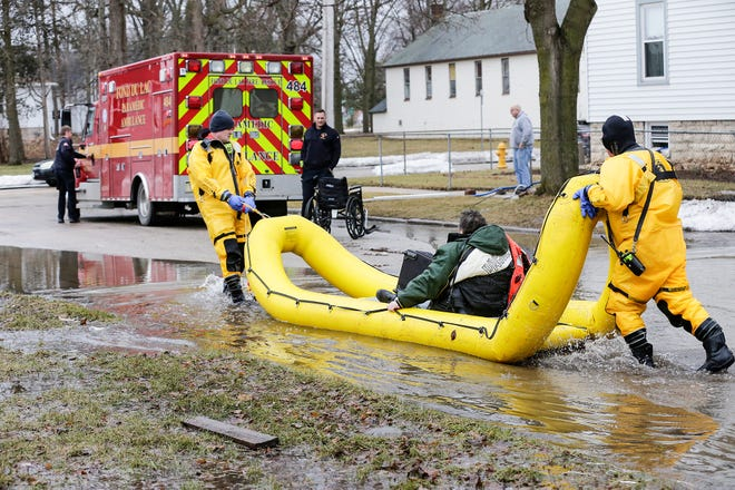 Fond du Lac Fire/Rescue members bring a woman to safety after evacuating her Friday, March 15, 2019, from her house on Gould Street in Fond du Lac, Wis. Ice jams on the east branch of the Fond du Lac River and heavy rain caused widespread flooding problems in the city on March 14.