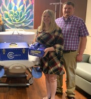 Tiffany and Trent Frisch stand next to a donated CuddleCot donated in their son Dawson's name.