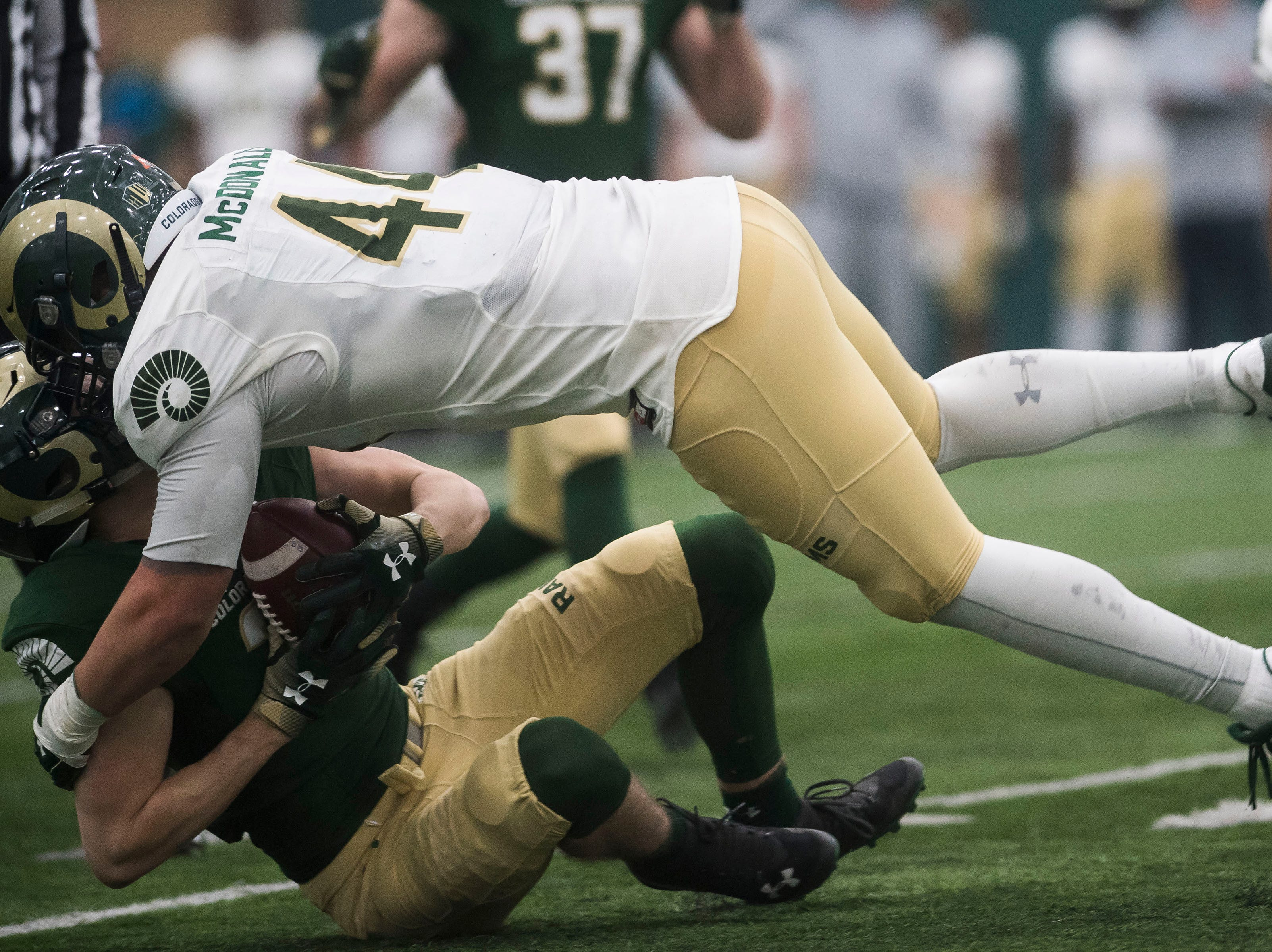 CSU freshman wide receiver Ryan Lynch (31) takes a hard shot from junior linebacker Max McDonald (44) during CSU's Spring game on Thursday, March 14, 2019, at their indoor practice facility in Fort Collins, Colo.